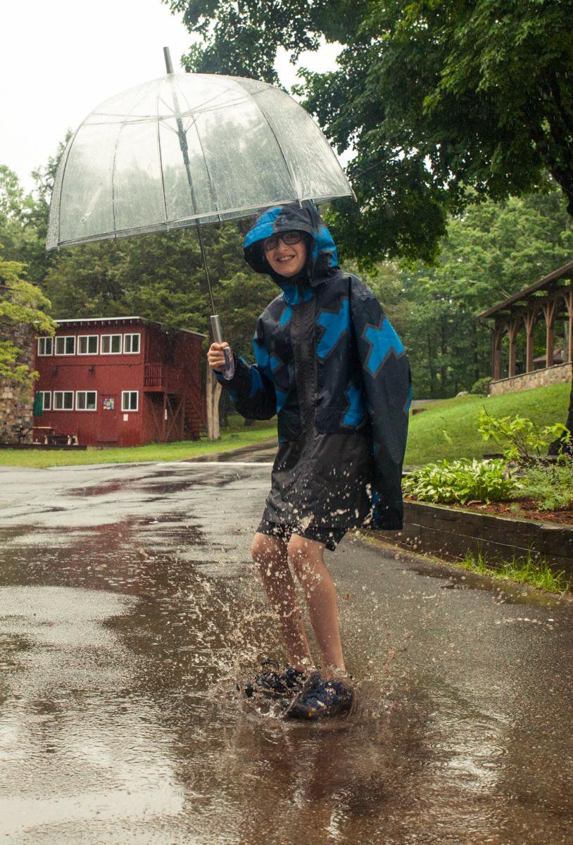 It rains at Camp. Pack rain gear! In the background: Simon House (left) and The Pavilion (right).