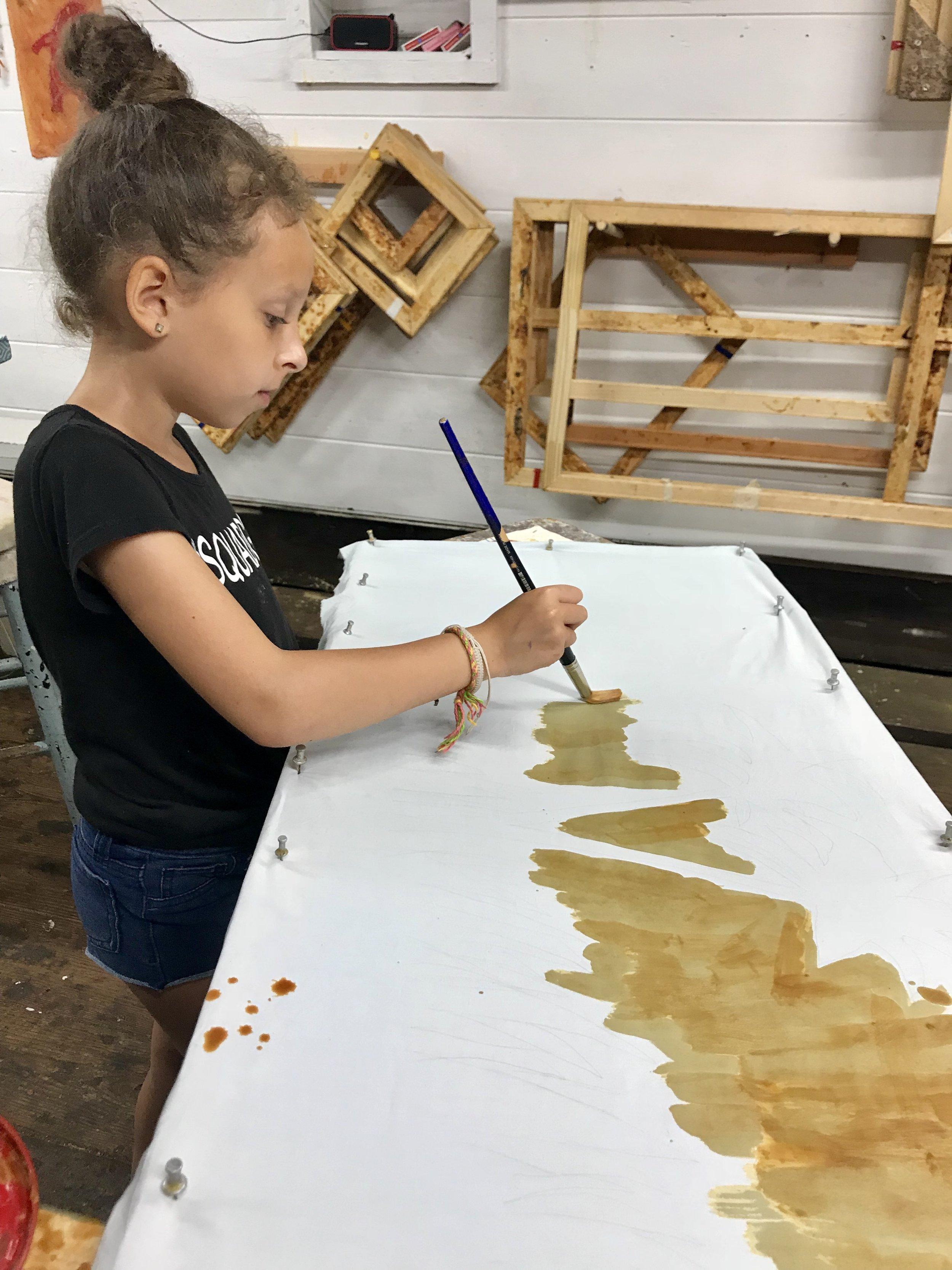 Painting wax on fabric.