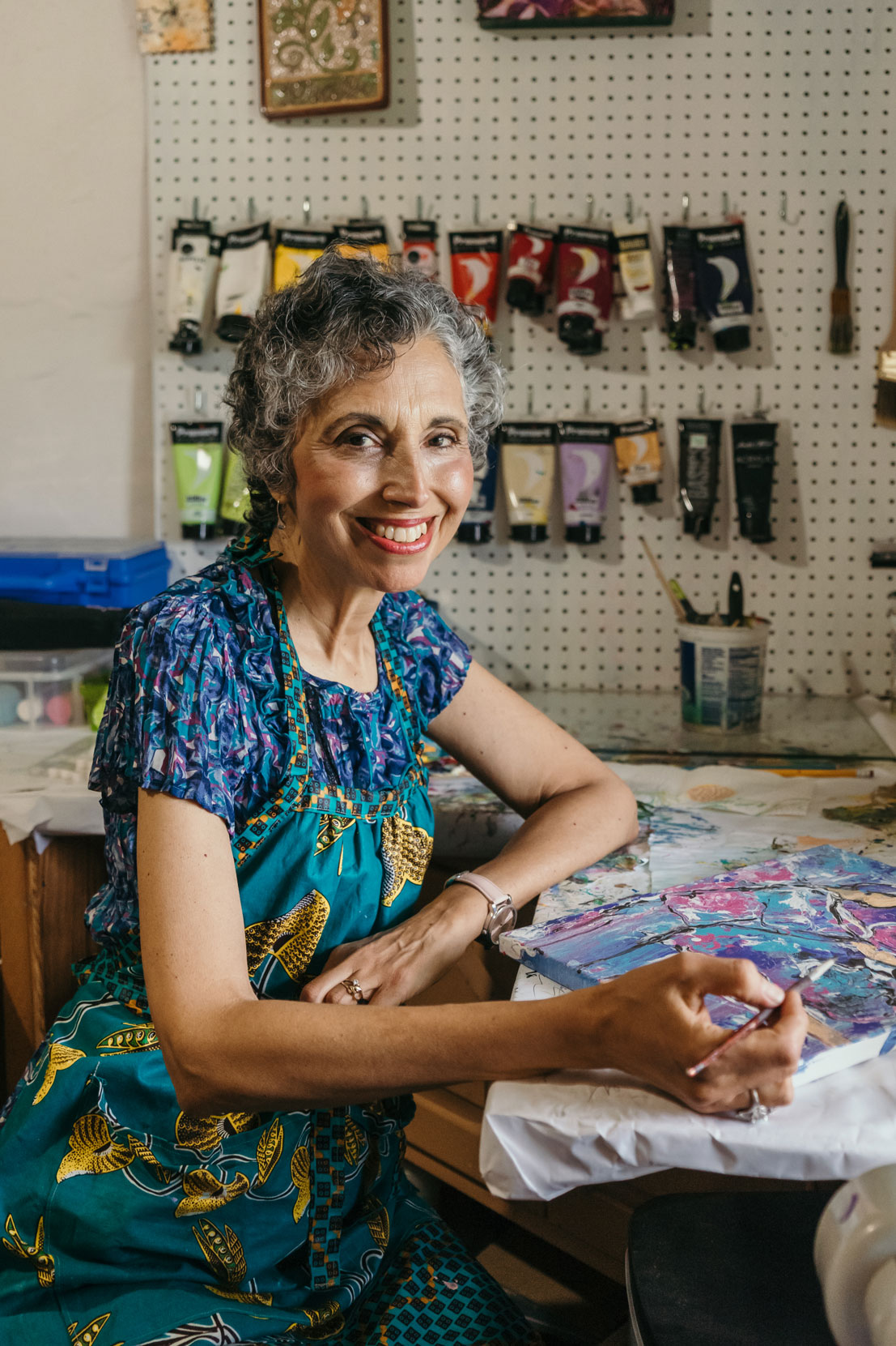 Painter Deborah Nell sits in her home studio in East Berlin, PA. Deborah's art features colorful pours and abstract figures.