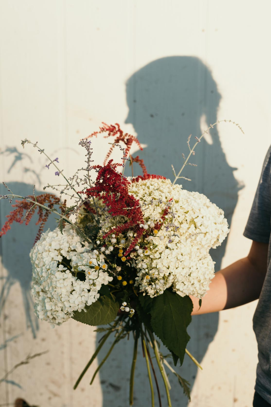 Georgia, 12, holds a bouquet of freshly-picked flowers on a farm in East Berlin, PA. Georgia said that posing for photos made her feel beautiful, even if her face wasn't shown.