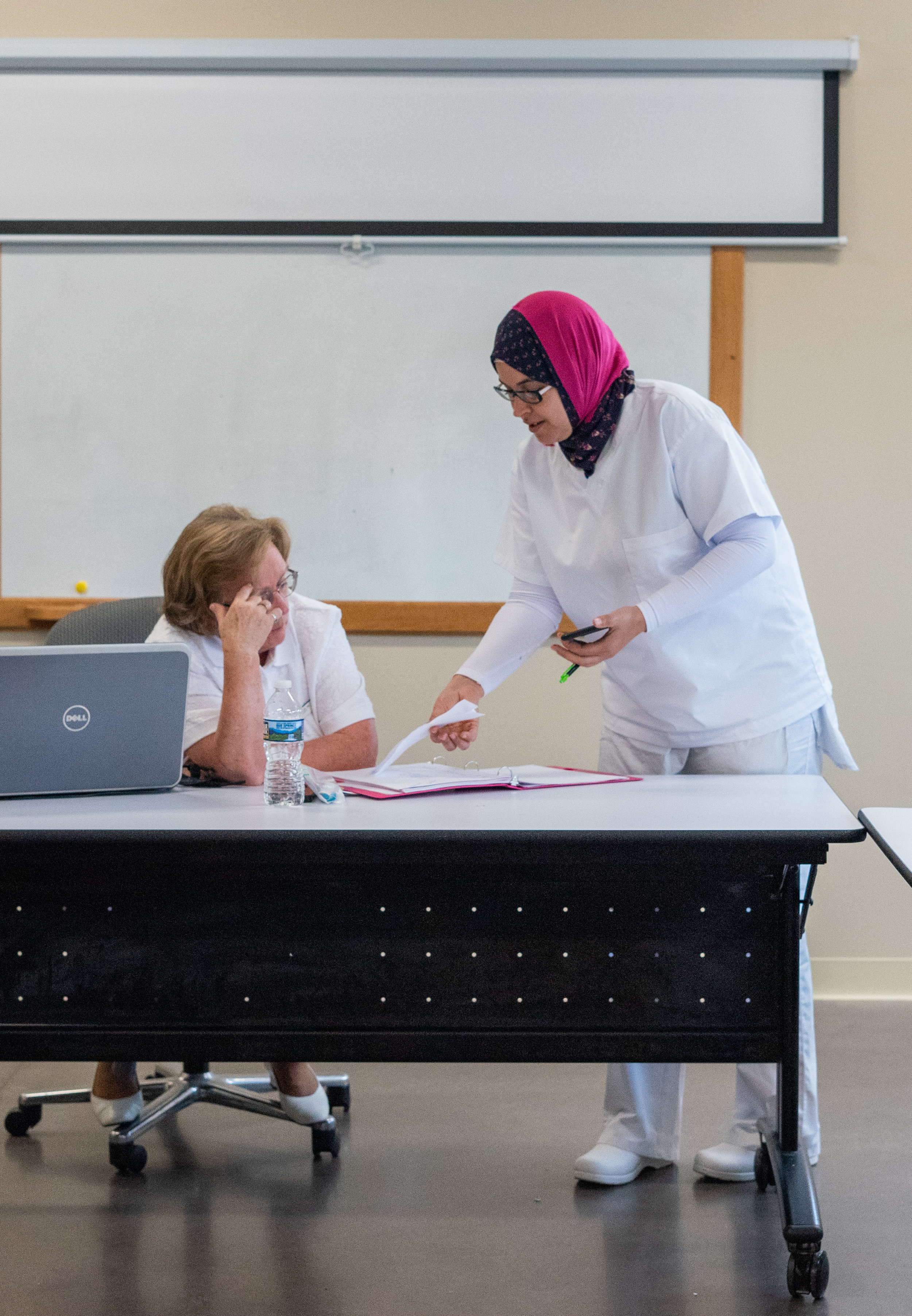 Nurse Aide program instructor helps a student with her work. The instructor has been teaching Nurse Aide programs at New Hope Ministries for 8 years and plans to continue for many more years to come.