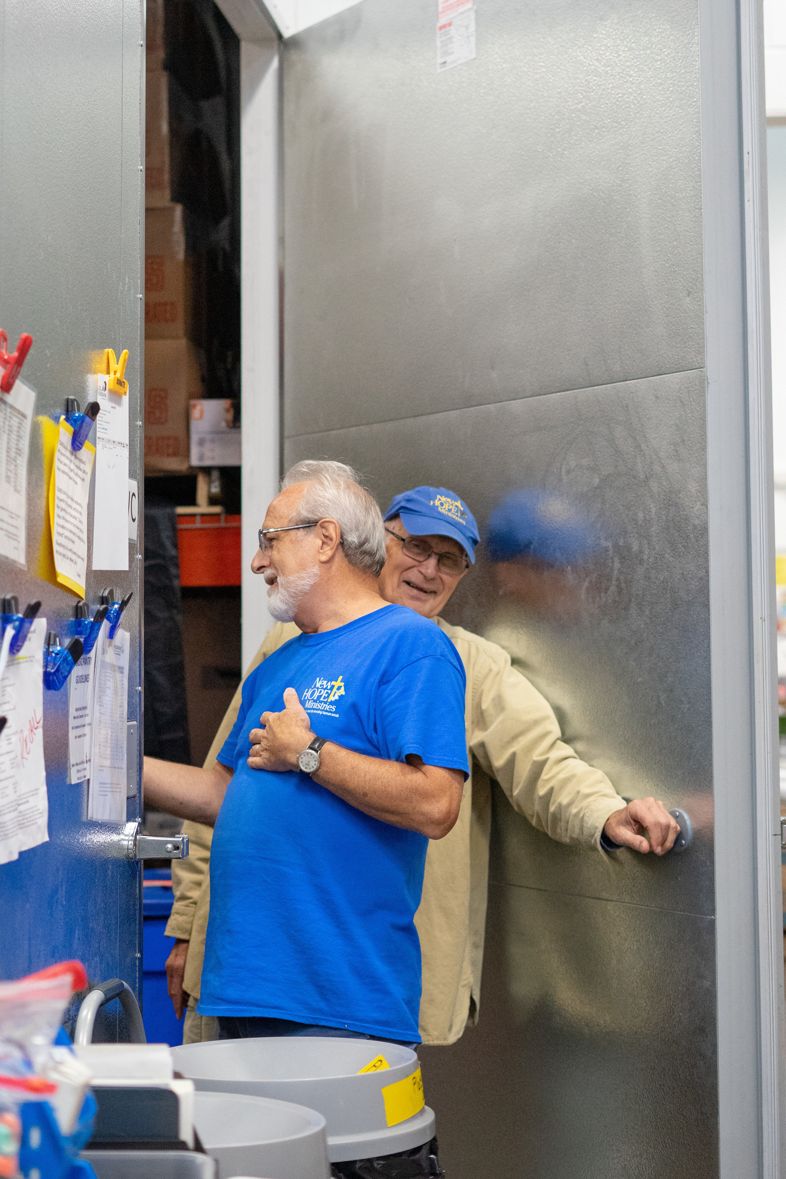Volunteers Dave (closest to camera) and Dick share a joke while volunteering at the food pantry. The pair has been working at the pantry for many years and have become friends with many of the volunteers and guests that come in to use the organization's services.