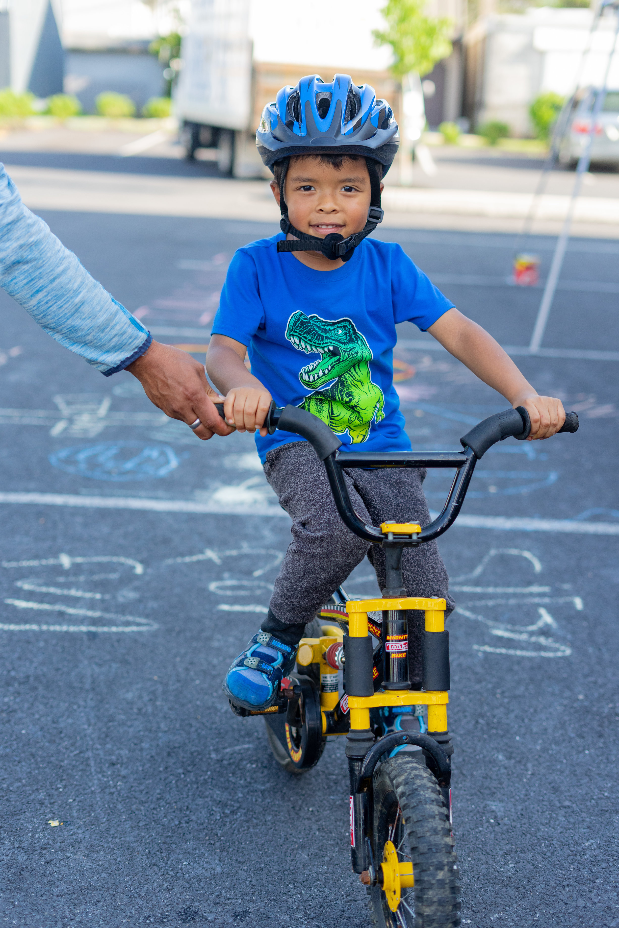 Noah G. poses with the bike he won in the Back-to-School fair raffle. Noah can't ride without training wheels yet, but is excited to learn.