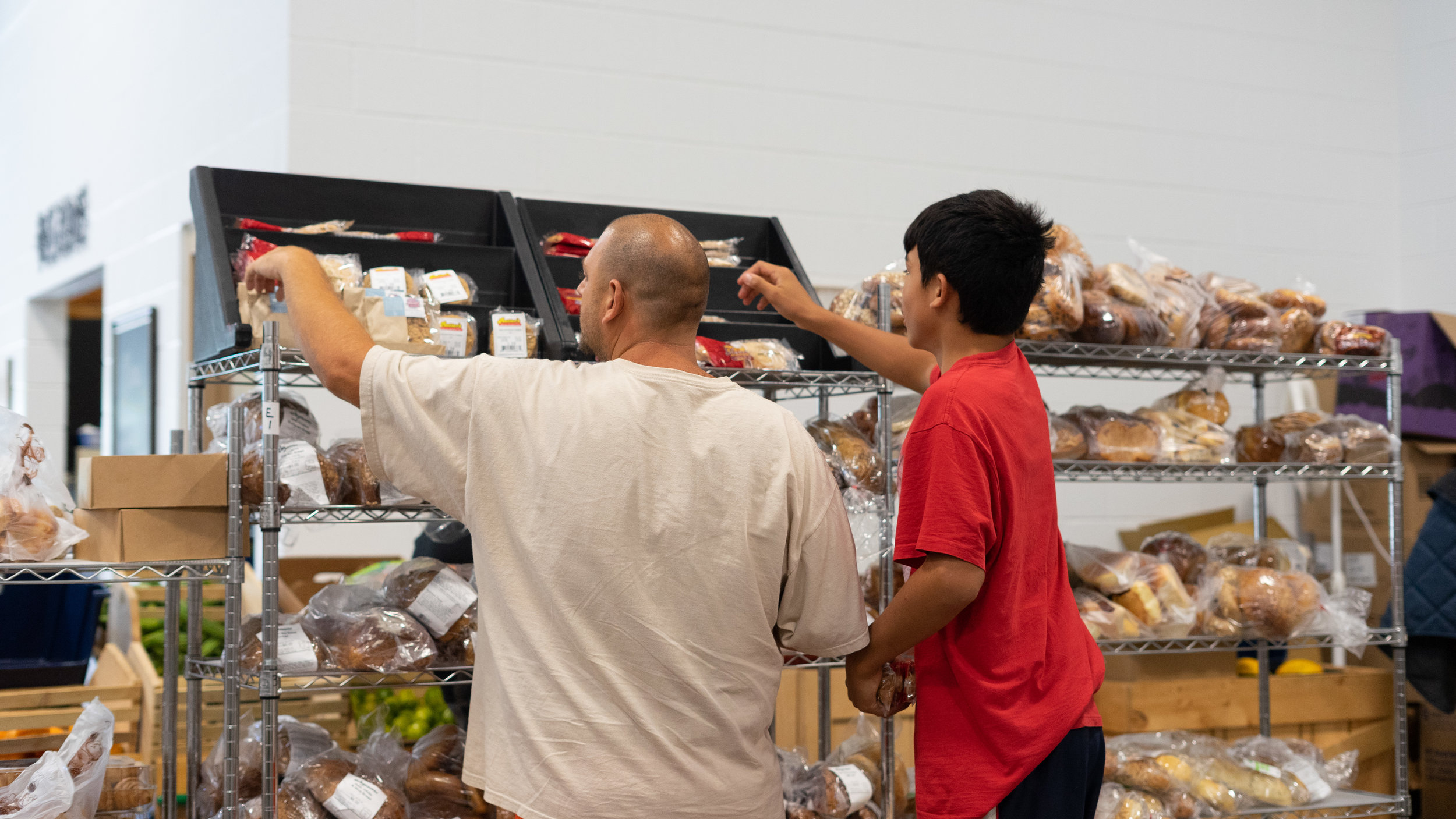 Mandy and his young friend Pete choose bread items from the food pantry. Guests may help themselves to unlimited bread items when they come in for their Food Pantry appointments.