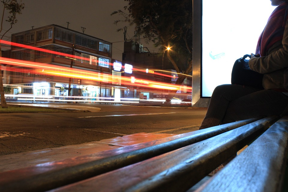 I am sitting on the cool metal bench of a bus stop. Waiting, but not for a bus. -