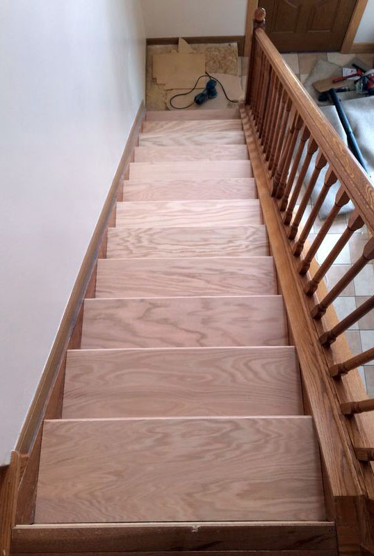 The new hardwood treads cut and fit over the existing treads. -