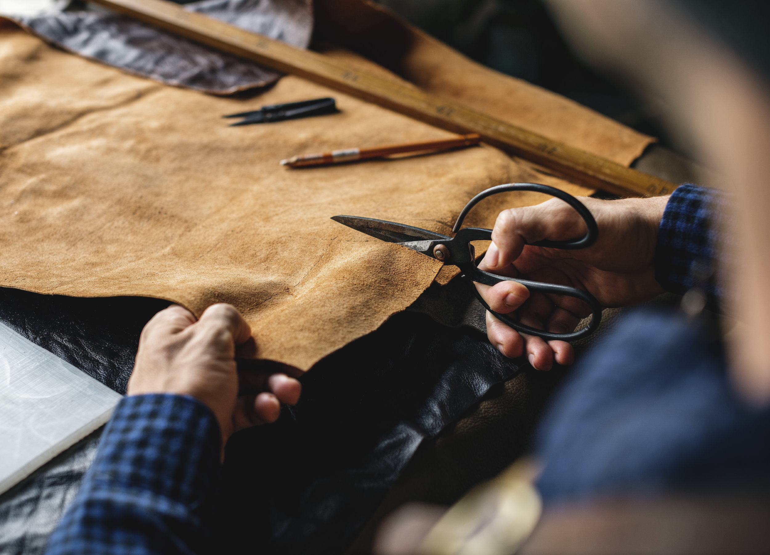 closeup-of-craftsman-cutting-leather-handicraft-P6HNJFZ.jpg