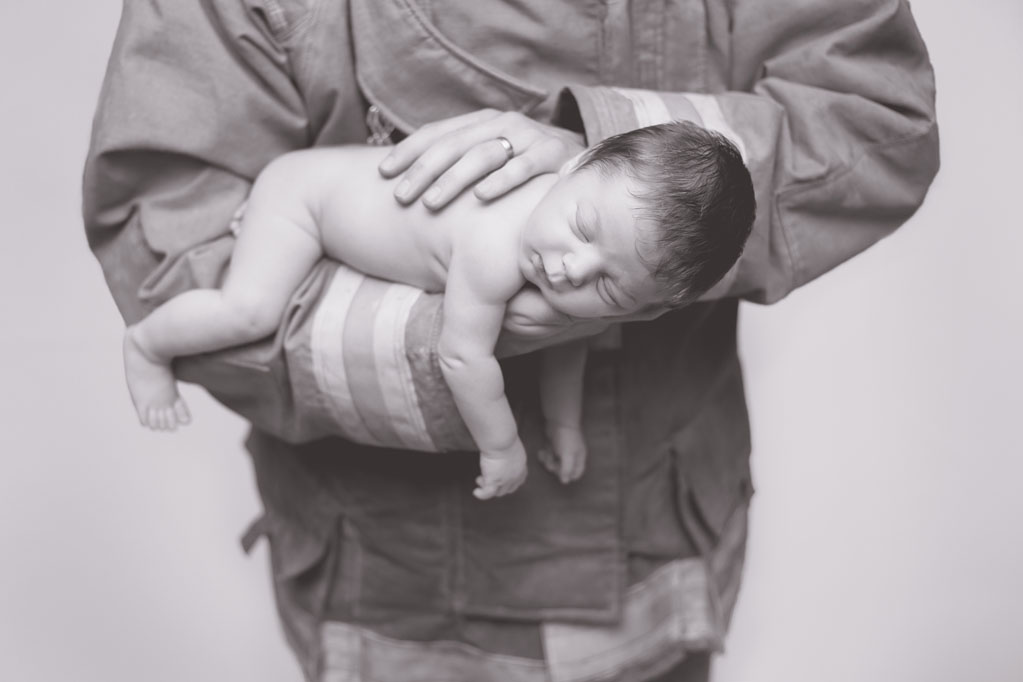 Baby Cooper posing with firefighter dad during baby pictures in San Diego CA
