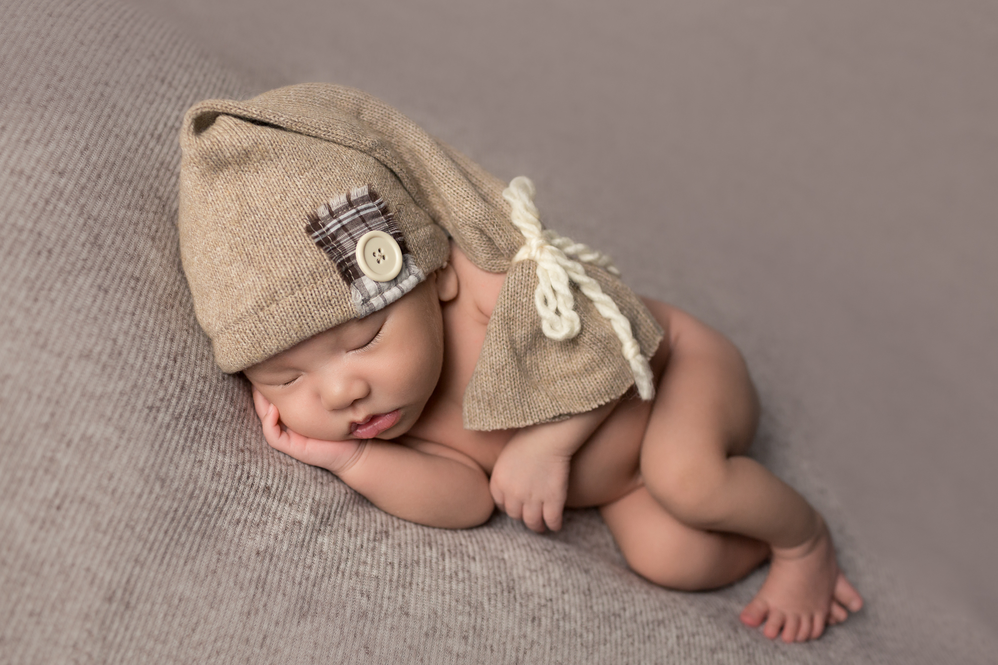 Newborn Baby Boy Rome with sleepy cap during newborn photography session in San Diego, CA