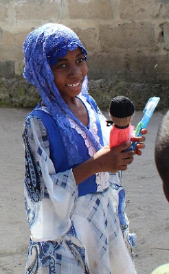 Happy with a doll and toothbrush