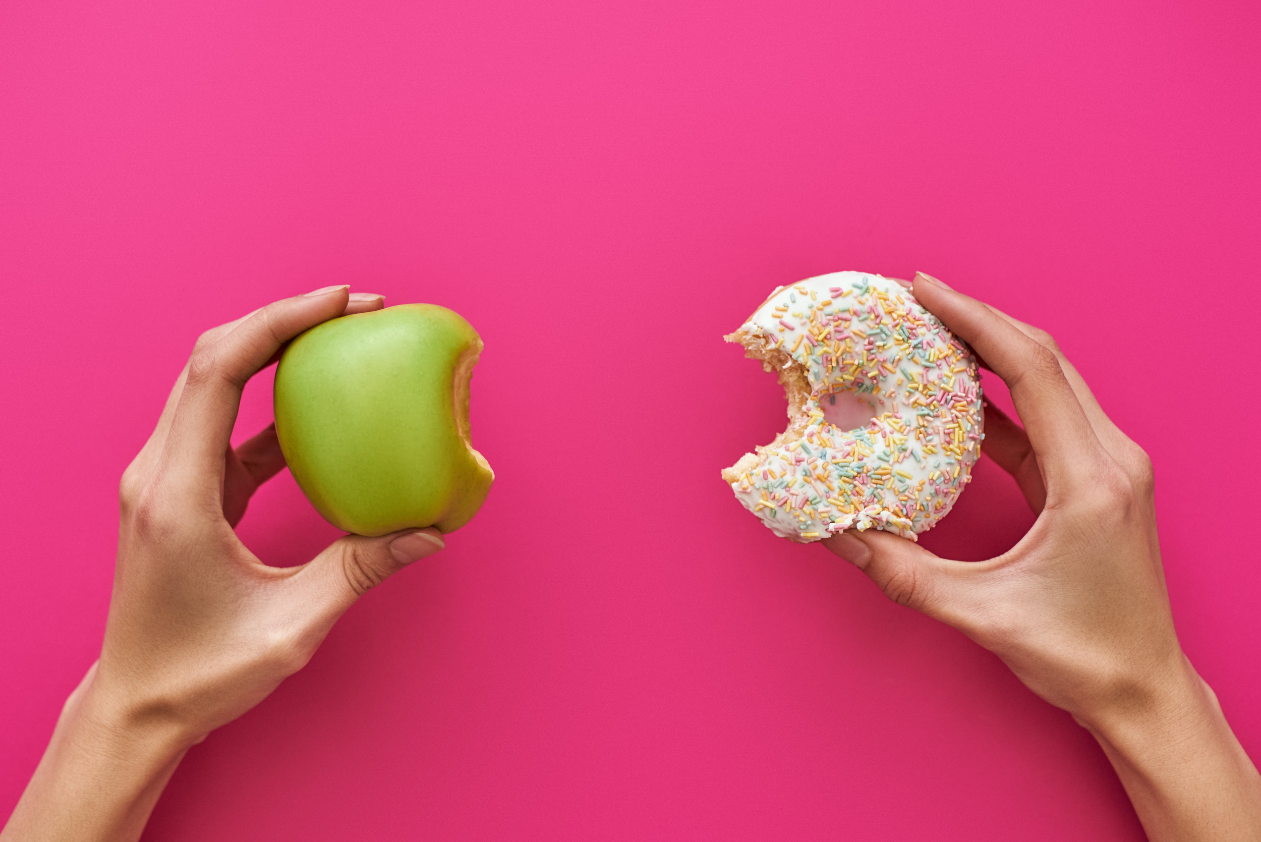 Dieting-or-good-health-concept.-Young-woman-trying-to-choose-between-apple-and-donut-1084344284_5904x3941.jpeg
