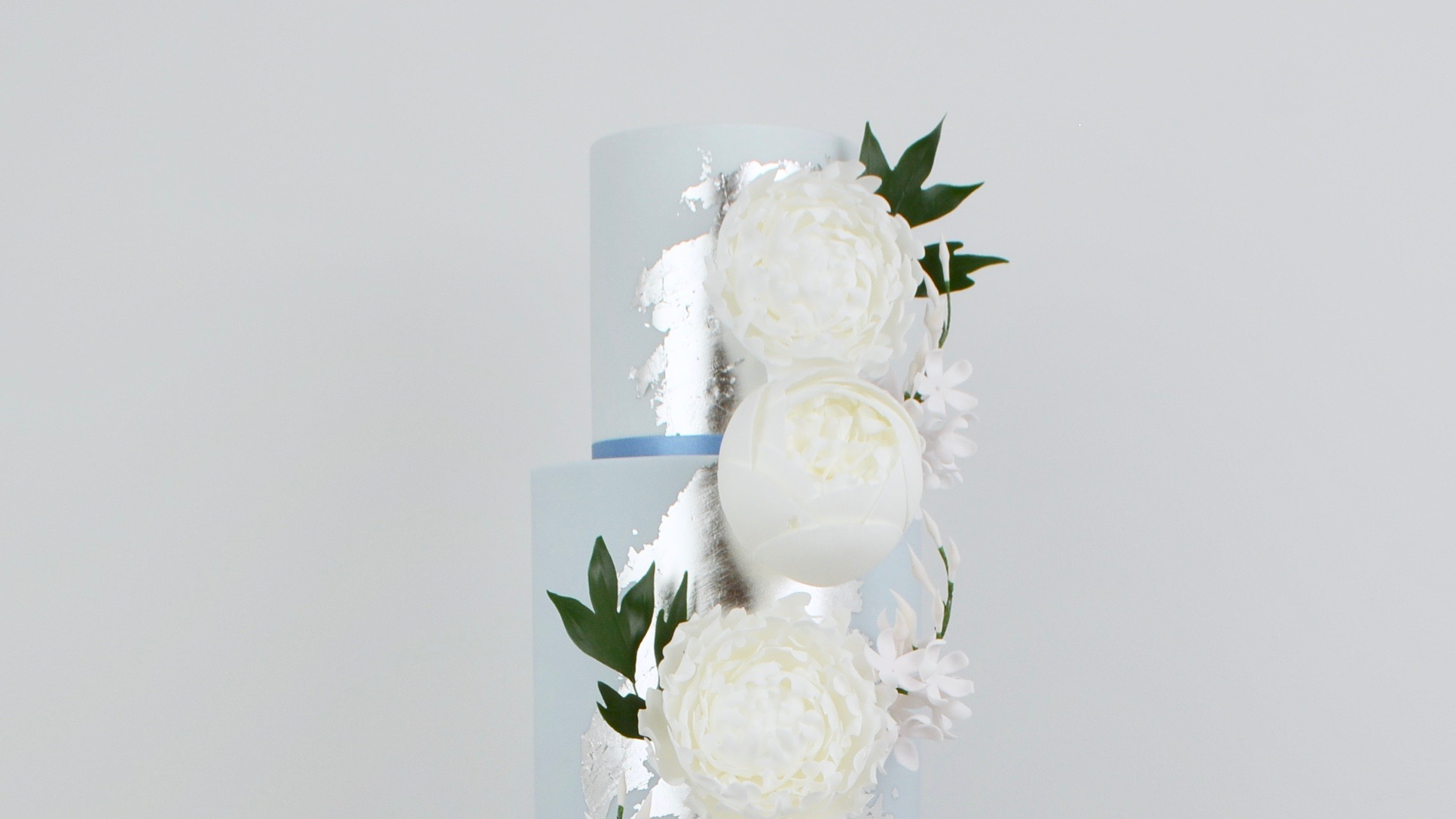 Dusky Blue and Peonies - An enchanting powder blue ombre wedding cake with flashes of edible silver leaf and a vertical cascade of beautiful white peonies and jasmine