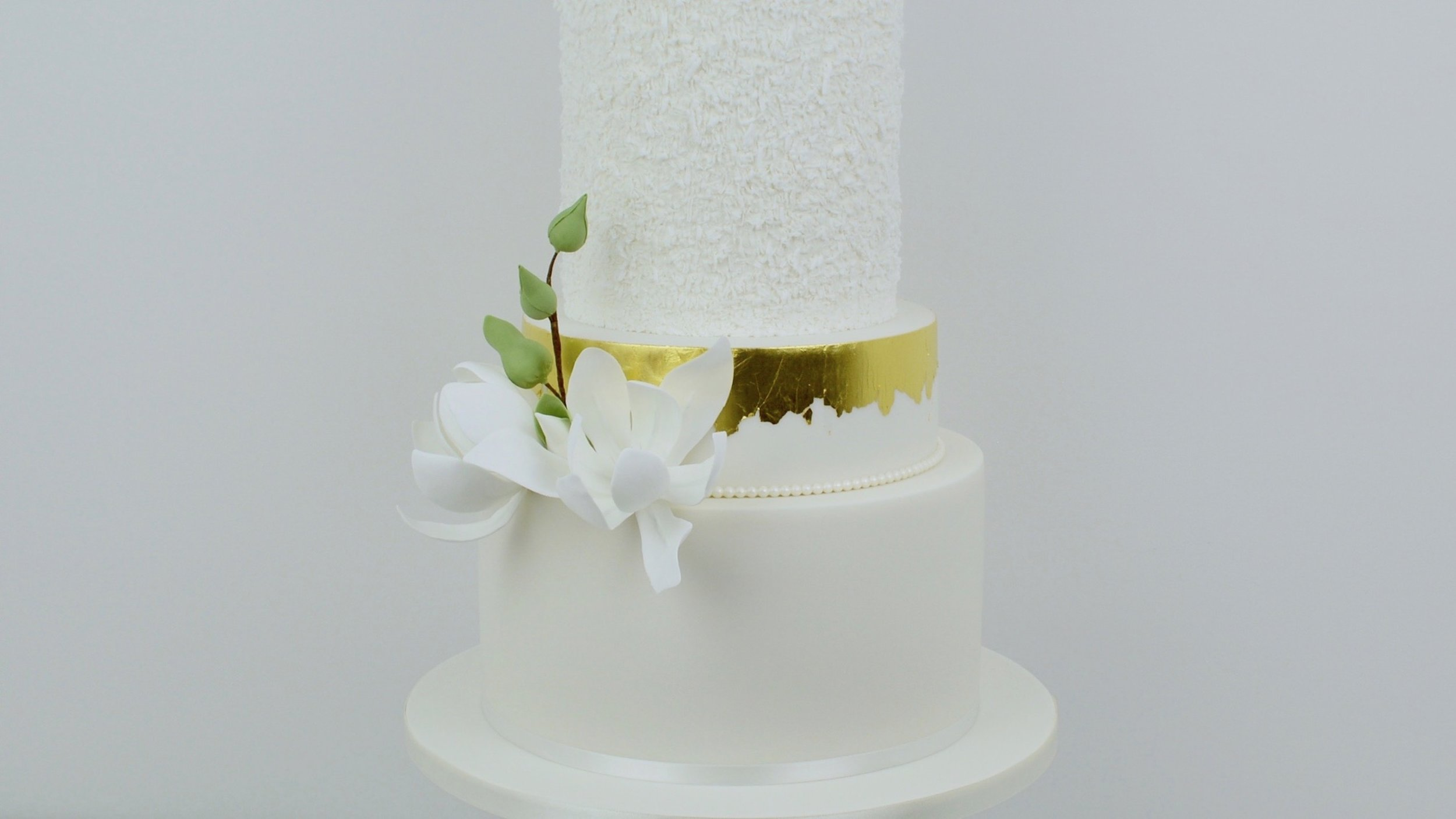 White Magnolias - Contemporary and timeless simplicity with striking magnolia sugar flowers for an elegant and sophisticated wedding cake