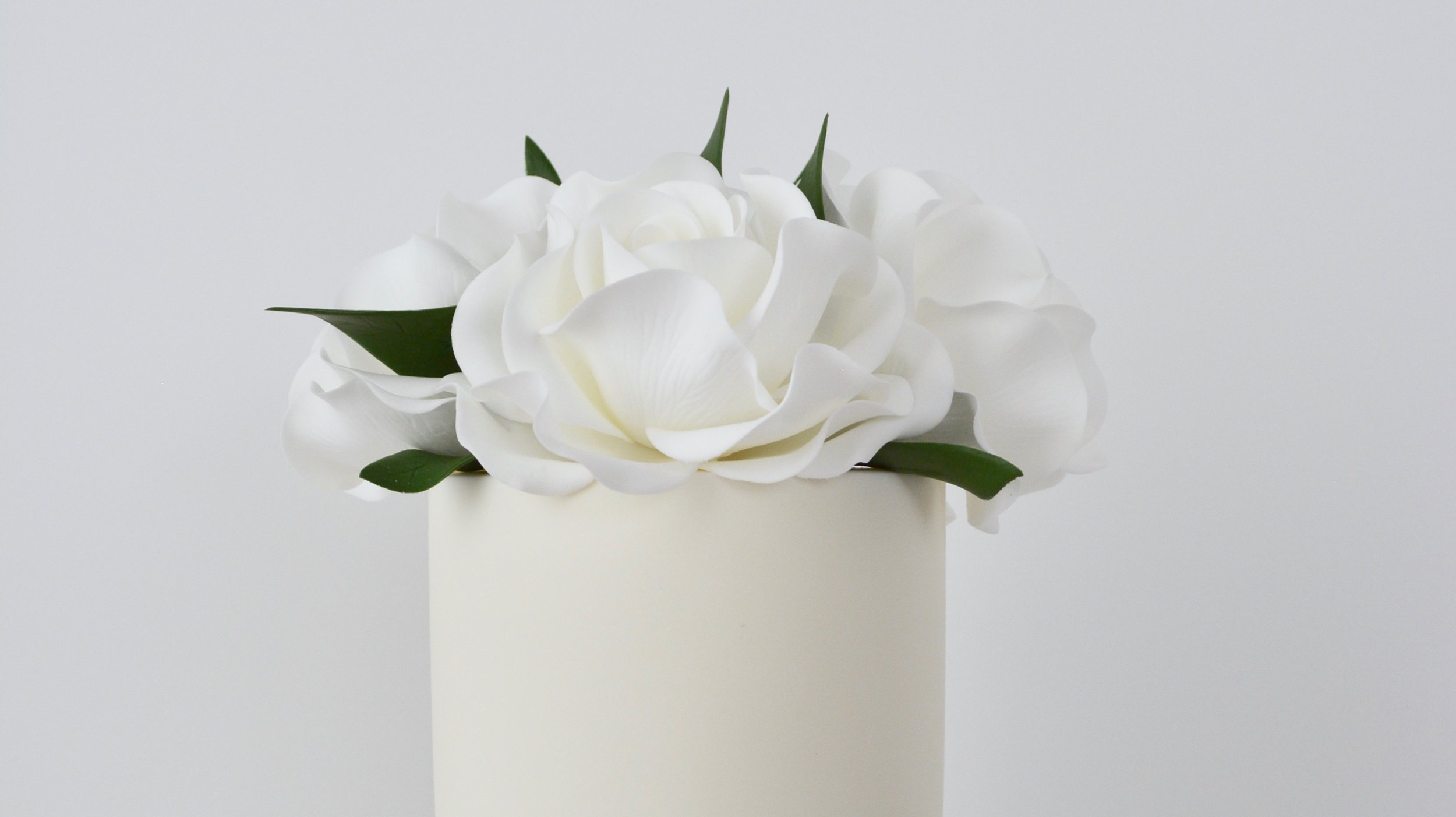 White Roses and Ranunculus - A marble icing tier contrasting striking white contemporary sugar roses, delicate ranunculus and poppy seed heads for an elegant showstopper