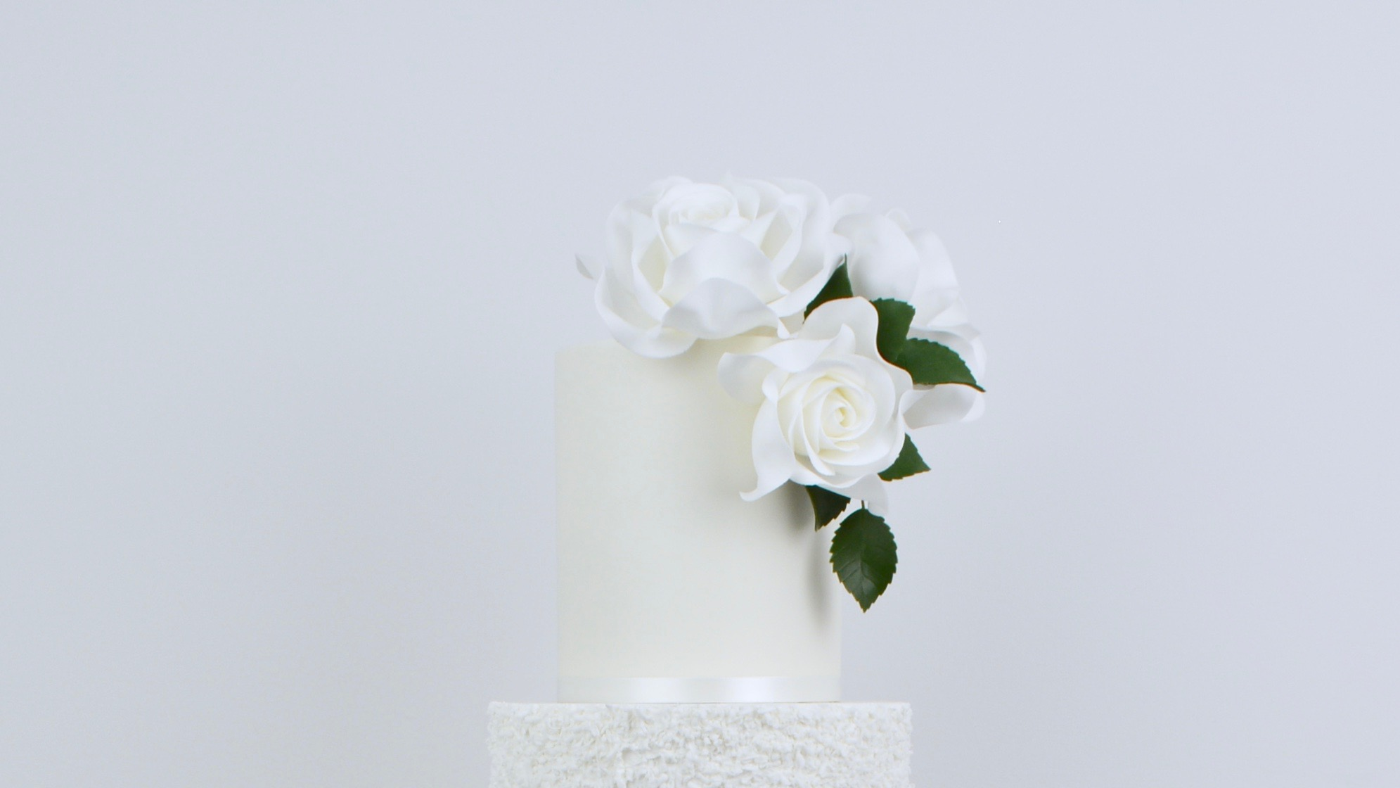 White Roses and Silver - A tall white textured tier with beautiful white roses, dark green foliage and silver leaf for a stylishly elegant wedding cake