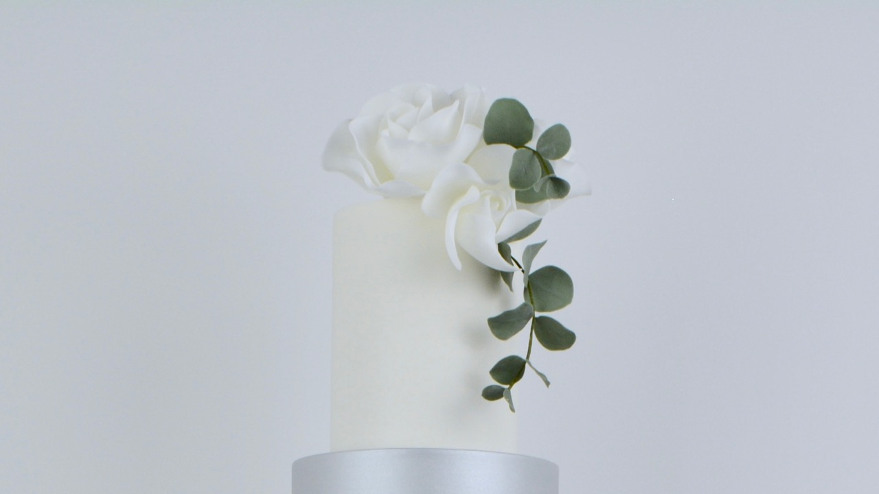 Roses and Silver Lustre - A beautifully elegant wedding cake with dreamy white roses, baby blue eucalyptus, a touch of shimmering silver and classic whites