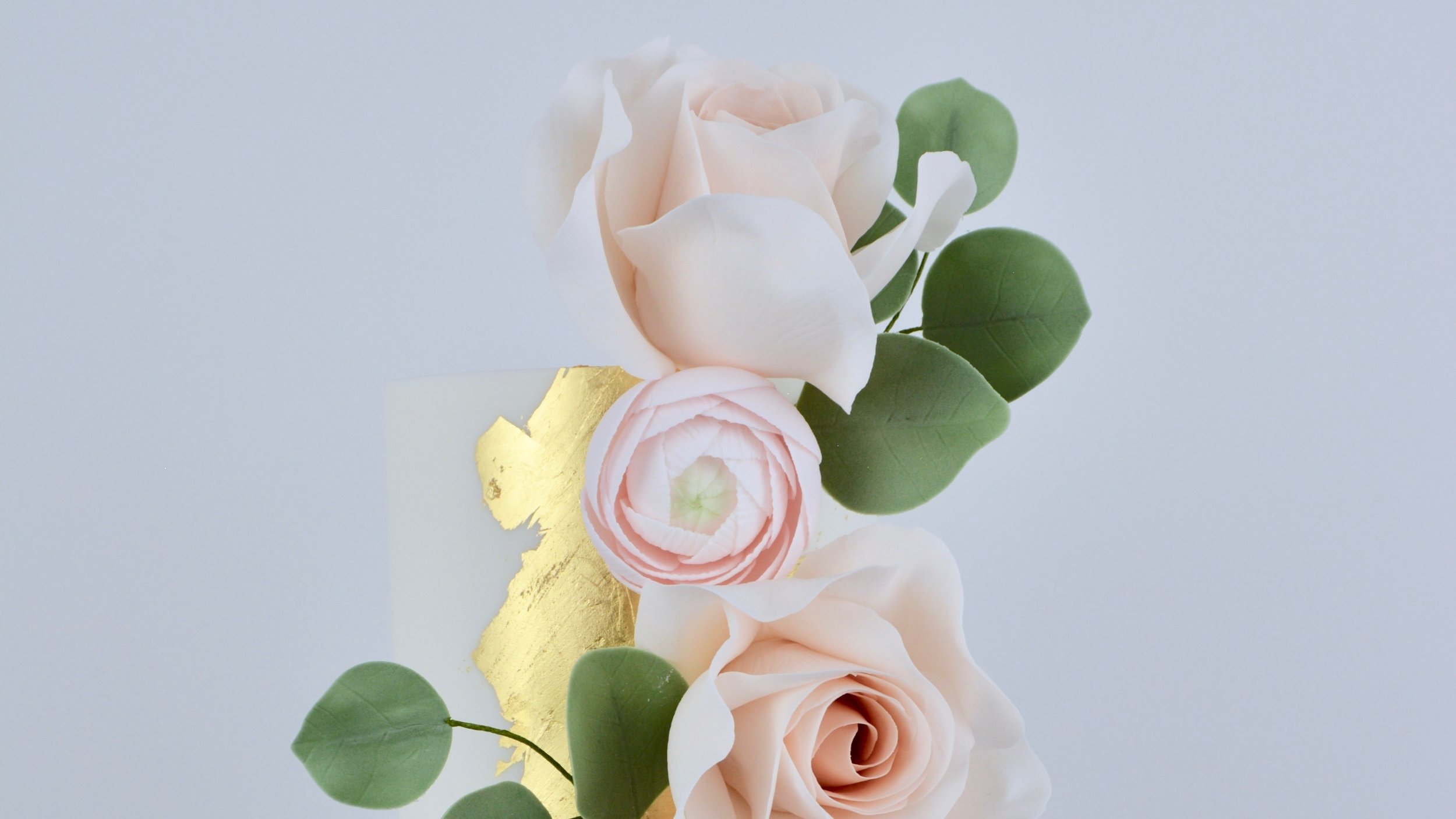 Rose Gold and Ranunculus - A gorgeous vertical cascade of delicate pink roses and ranunculus against a striking edible gold leaf and grey marble icing for a shimmering spectacular wedding cake