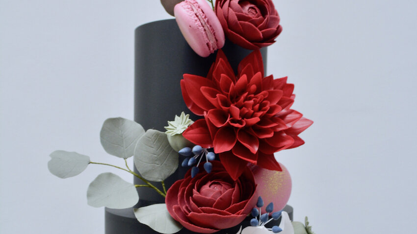 Autumn Blooms - Rich Autumnal colours with a vibrant cascade of burgundy dahlias, cafe au lait dahlia and chocolate ranunculus in a striking design for an alluring centrepiece