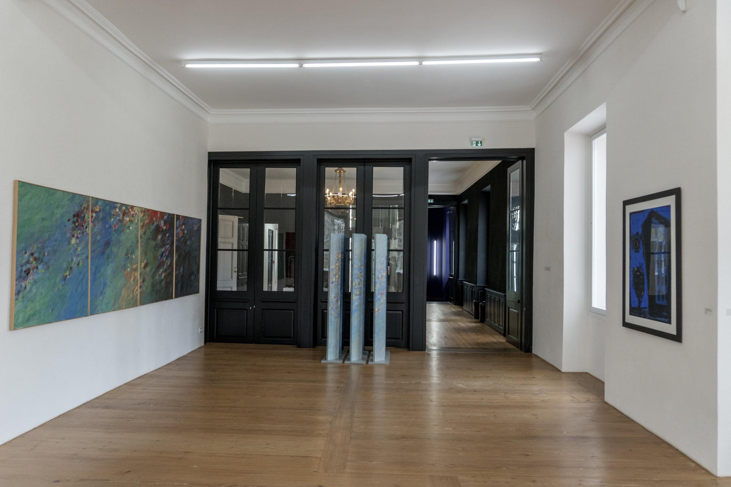Boiseries noires et plancher de bois blond où faire glisser des souliers de bal, sous un lustre ancien en bronze doré... en contre-point de la sérénité fluide et colorée de deux oeuvres récentes d'  Emil Kiess.