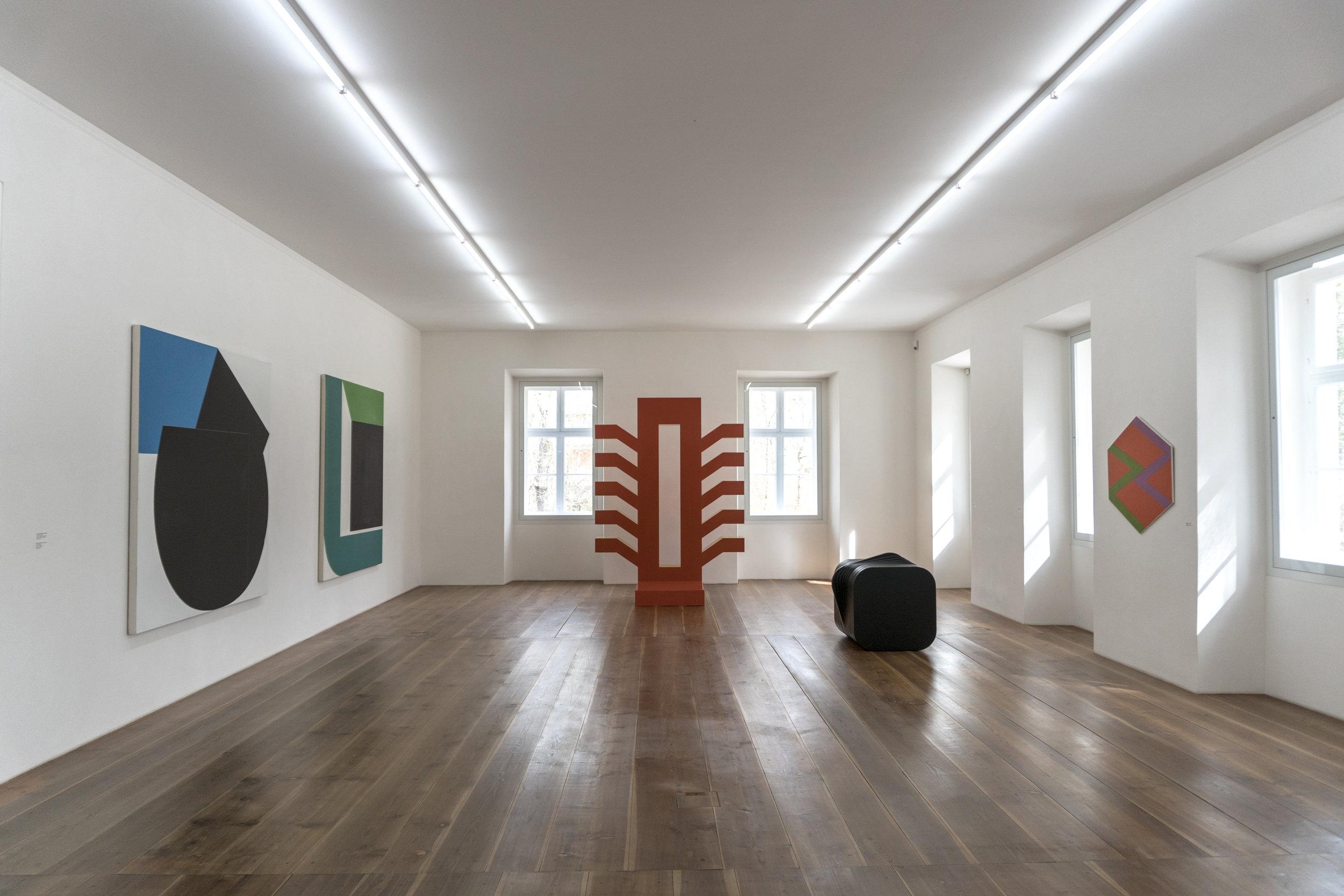 """Exposition  """"colorful. farbenfroh""""  (2018). Oeuvres de:  Otto Herbert Hajek  (au centre): """"Farbwege 68/6"""" (1968) -  Georg Karl Pfahler  (à gauche): """"Achmed II"""" (1978/79) et """"S-RB"""" (1967/68) -  Thomas Lenk  (sur le plancher, à droite): """"Schichtung 13 (Orkel)"""" -  Winfred Gaul : """"Jazz Sex-a-gon"""" (1967)"""
