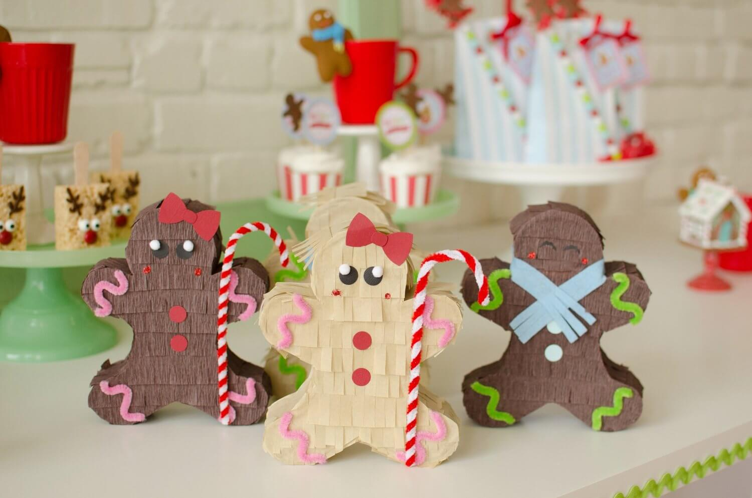 These gingerbread man pinatas are the cutest holiday party decor for a Christmas cookie decorating party. See more from this Cookies for Santa party on www.minteventdesign.com - styled by Austin, Texas based party planner Mint Event Design. #holidayparty #holidaypartyideas #christmaspartyideas #pinatas #gingerbreadman #cookieparty