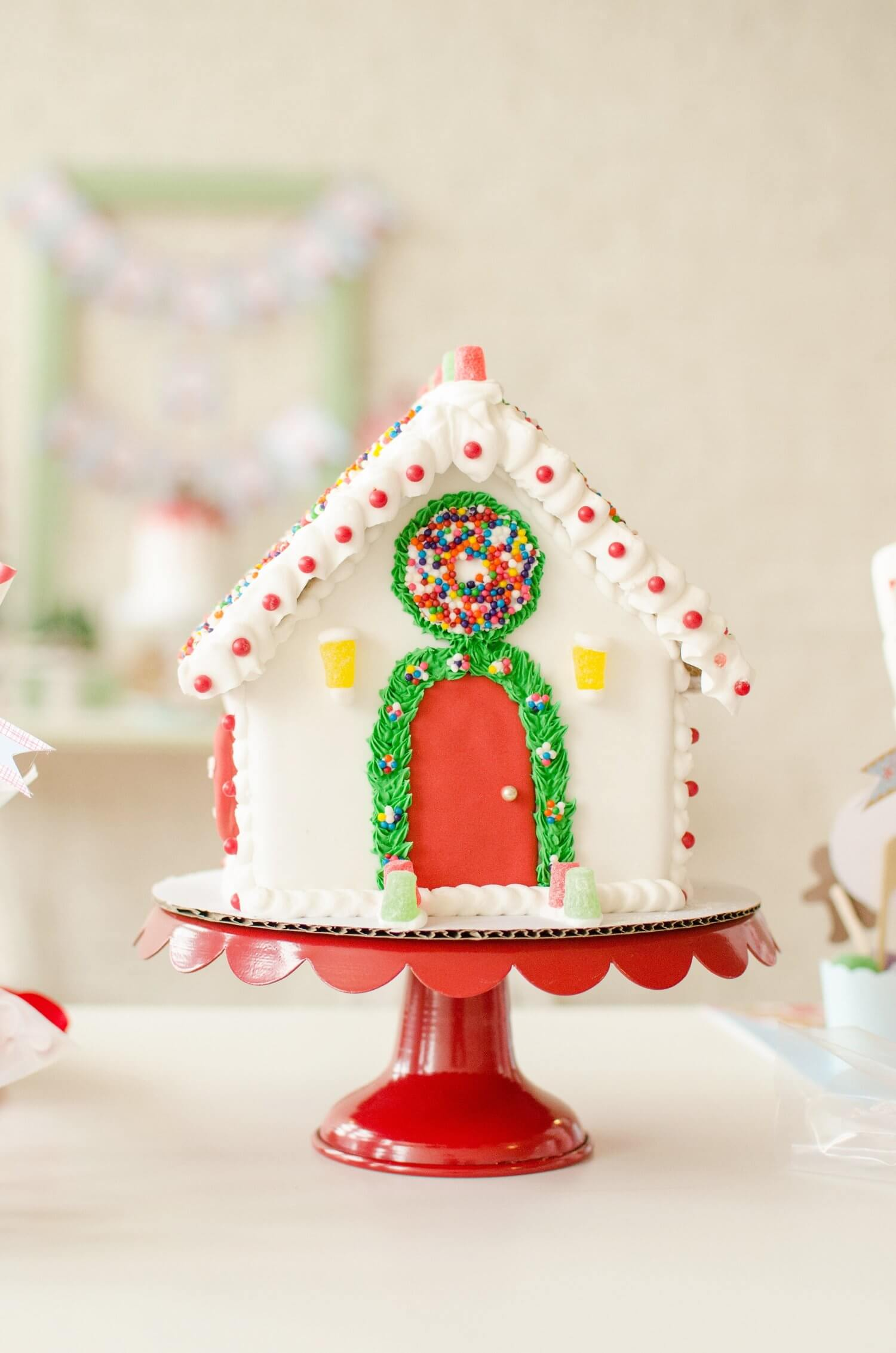 A pretty frosted Gingerbread house on a red pedestal cake stand creates the perfect holiday centerpiece for Christmas parties. See more from this Cookies for Santa party on www.minteventdesign.com - styled by Austin, Texas based party planner Mint Event Design. #holidayparty #holidaypartyideas #christmaspartyideas #gingerbreadhouse #gingerbreadhouseideas