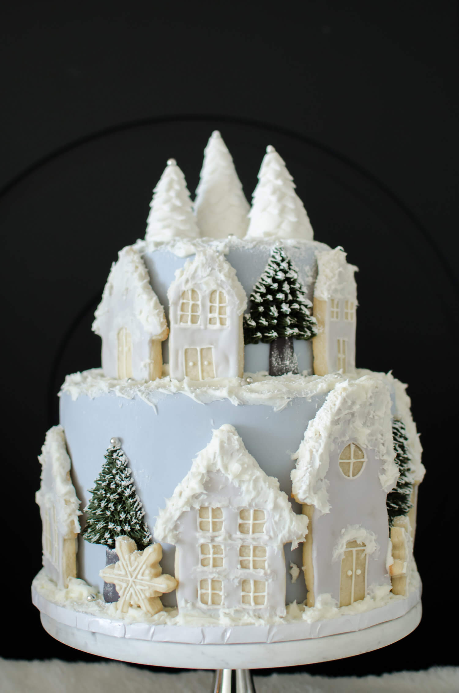 Winter Bridal Shower Cake Idea with a snowy village scene created with frosted cookies and trees. See more from this Winter Wonderland themed Bridal Shower Inspiration created by Mint Event Design www.minteventdesign.com #winterweddingideas #weddingwedding #bridalshowerideas #winterwonderland #wintercake #bridalshowercakes #weddingcakes