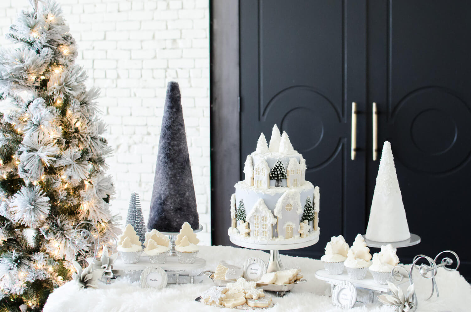 The prettiest of Winter Party Dessert Table Inspiration. Snow flocked tree, a cake decorated with cookies and edible cookies top the cupcakes. See more ideas from this Winter Wonderland themed Bridal Shower Inspiration created by Mint Event Design www.minteventdesign.com #winterweddingideas #weddingwedding #bridalshowerideas #winterwonderland #desserttable