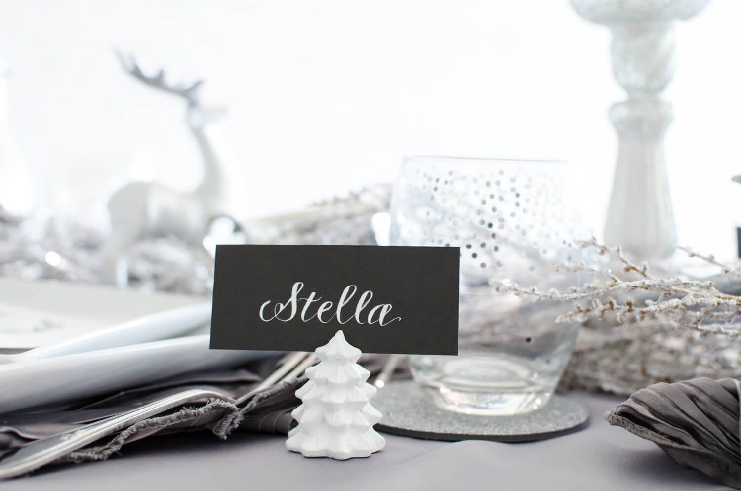 Cute white tree place card holder with hand calligraphed place card. See more ideas from this Winter Wonderland themed Bridal Shower Inspiration created by Mint Event Design www.minteventdesign.com #winterweddingideas #weddingwedding #bridalshowerideas #winterwonderland #placecard #calligraphy