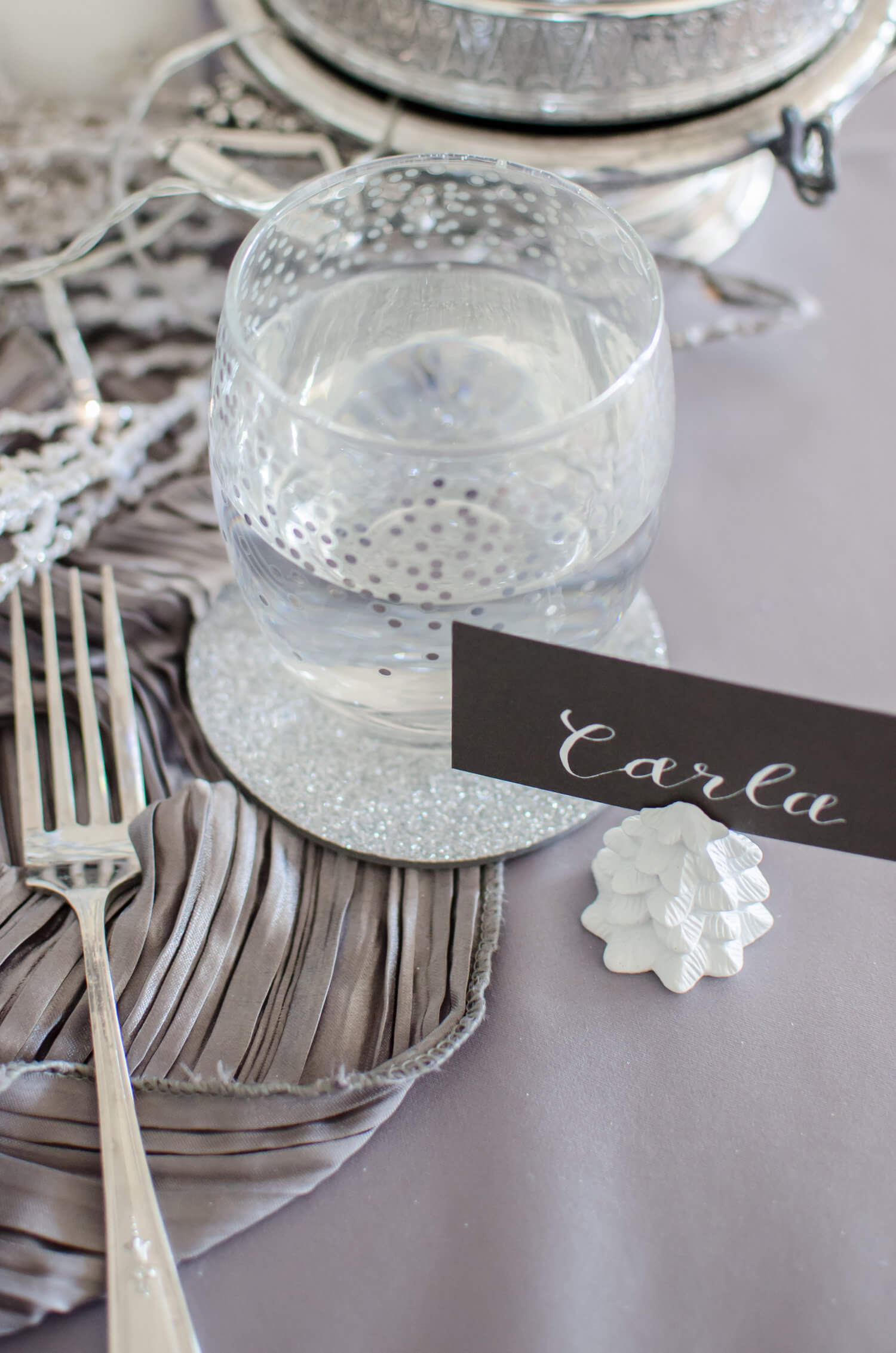 The perfect winter wonderland tablesetting details - silver glitter coasters, confetti glasses, and shimmery grey rouched linens. See more ideas from this Winter Wonderland themed Bridal Shower Inspiration created by Mint Event Design www.minteventdesign.com #winterweddingideas #weddingwedding #bridalshowerideas #winterwonderland