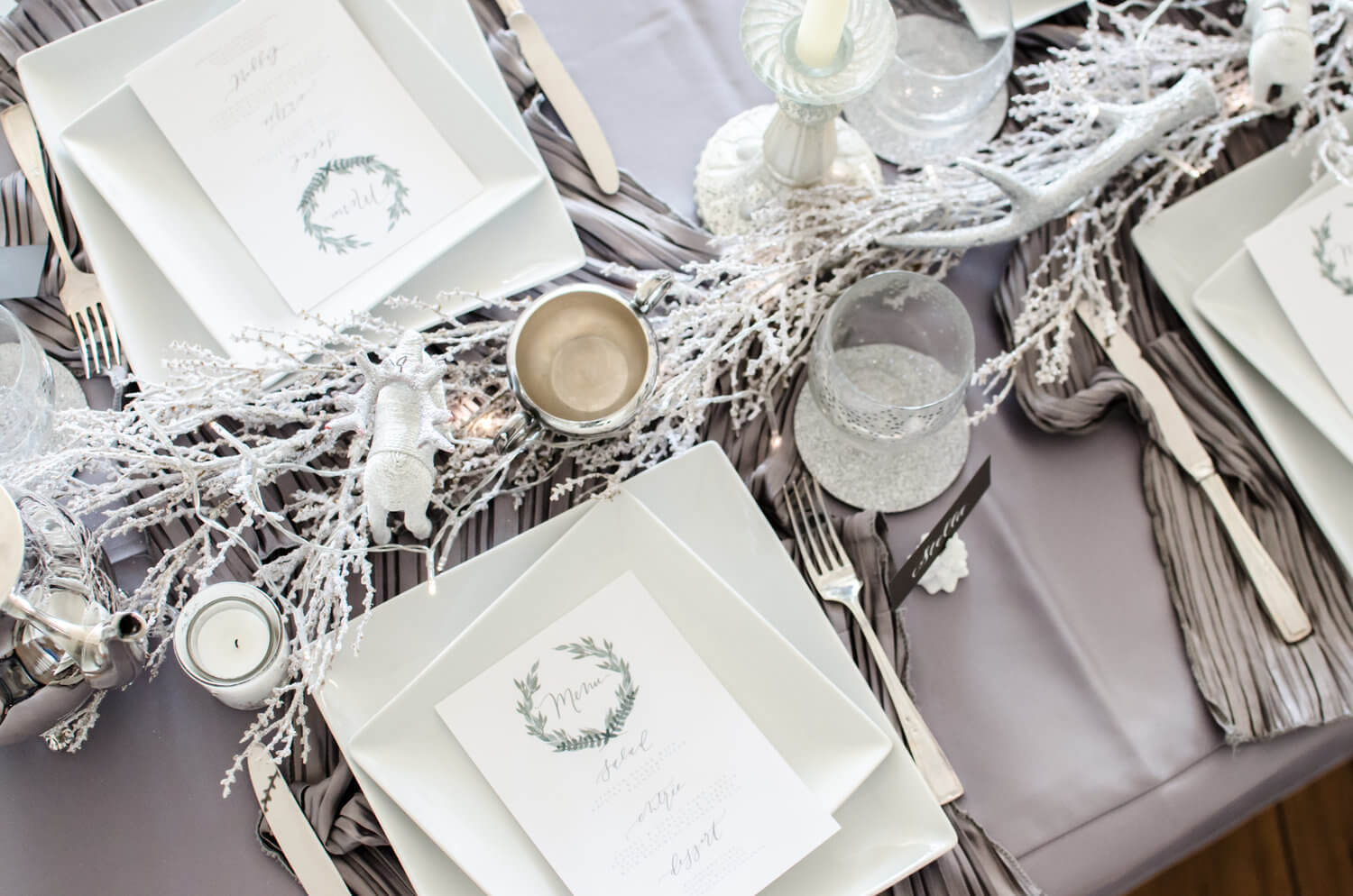 Pretty white and grey tablescape for a winter party. Table runner created with polar bears, antlers and white branches. See more ideas from this Winter Wonderland themed Bridal Shower Inspiration created by Mint Event Design www.minteventdesign.com #winterweddingideas #weddingwedding #bridalshowerideas #winterwonderland #tablescapes #tablesettings