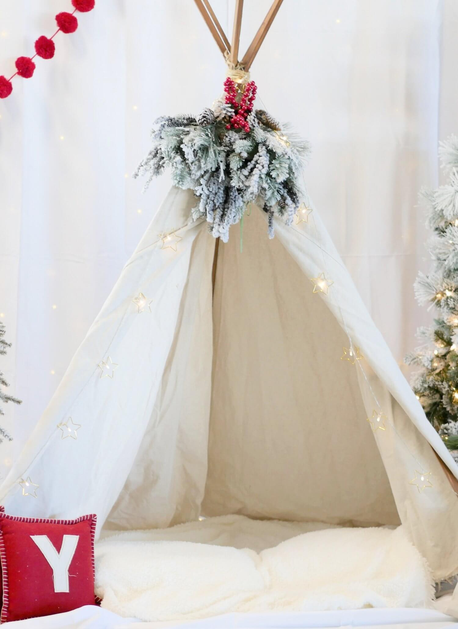When creating a holiday photo booth for family and friends - look for props at home before heading out to shop. This teepee was from a boho birthday party and provided the perfect photo booth prop. Click for more Photo Booth Tips from Mint Event Design www.minteventdesign.com #holidayphotography #photoboothideas #christmaspartyideas #photobooth #holidayparties