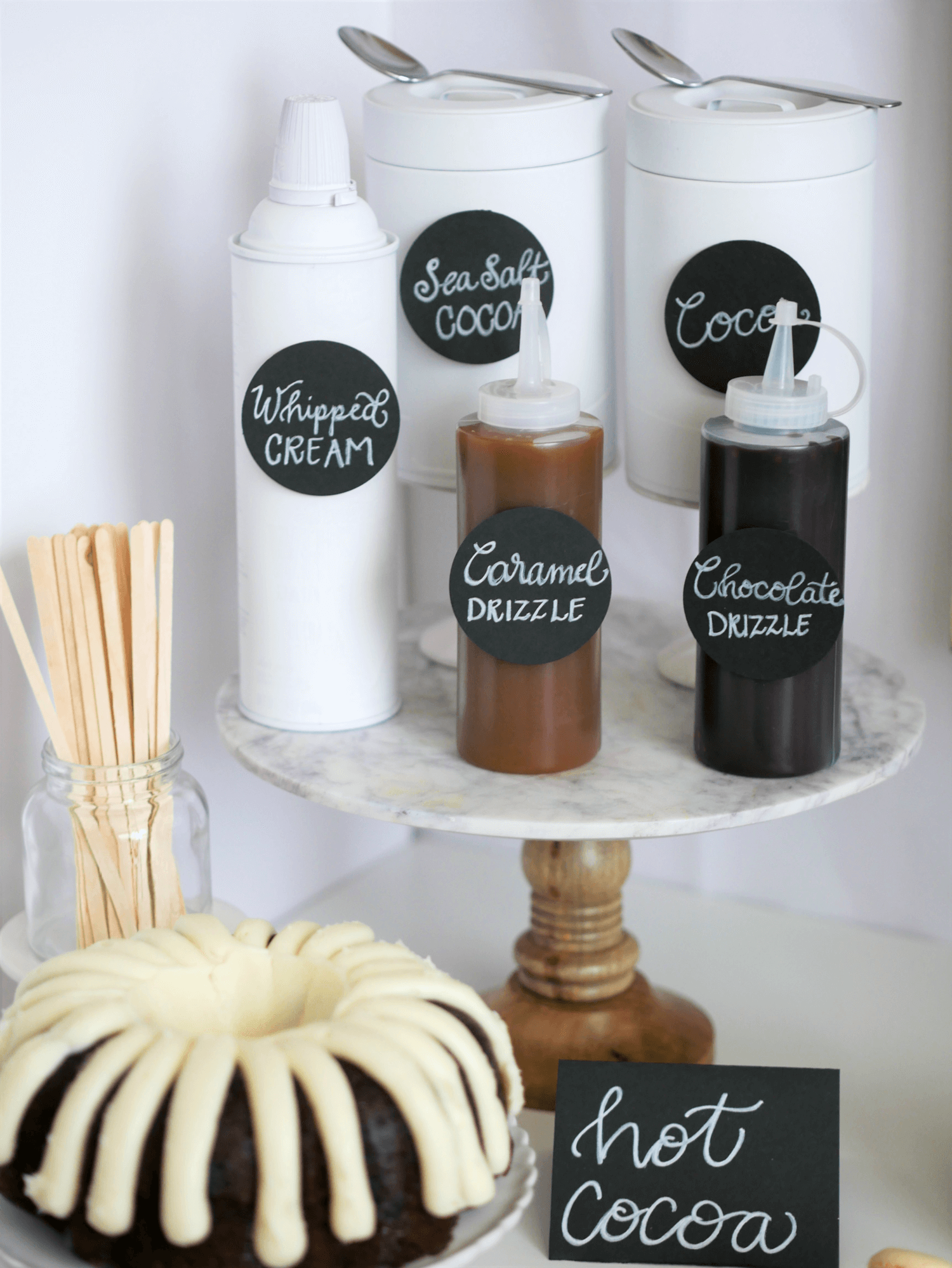 A Nothing Bundt Cake in Chocolate Chip Flavor is the special desert in this DIY Hot Cocoa and Coffee Station with special drizzle sauce for the drinks. Styled by party stylist Mint Event Design. #partyideas #partyinspiration #hotchocolate #hotcocoa #coffeebar #coffeestation #winterparty #winterwedding #bundtcake