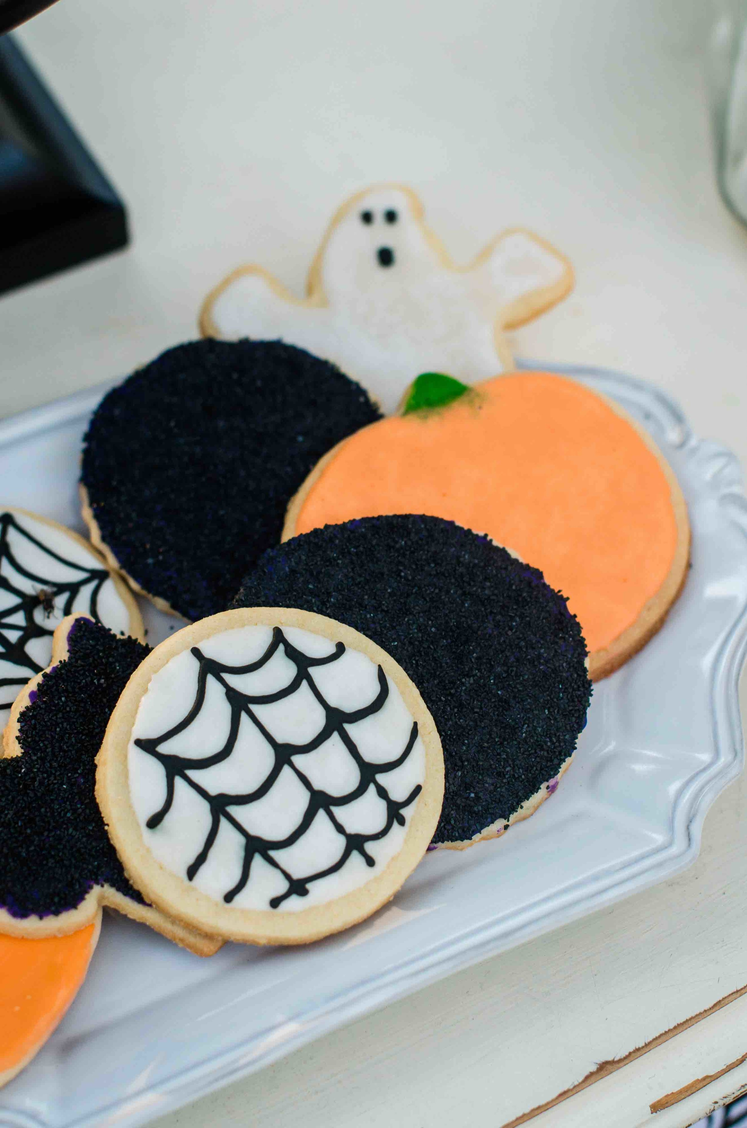 Amazing Halloween Party Cookies decorated with glittery sugar and cobwebs. Halloween Cookies include ghosts, pumpkins and spider webs. Click to see all the Halloween Party Ideas that you can re-create for your very own Halloween Kids Party. Styled by party stylist Mint Event Design. #halloween #partyideas #partyinspiration #partydecor #desserttable #halloweencookies #halloweendecorations