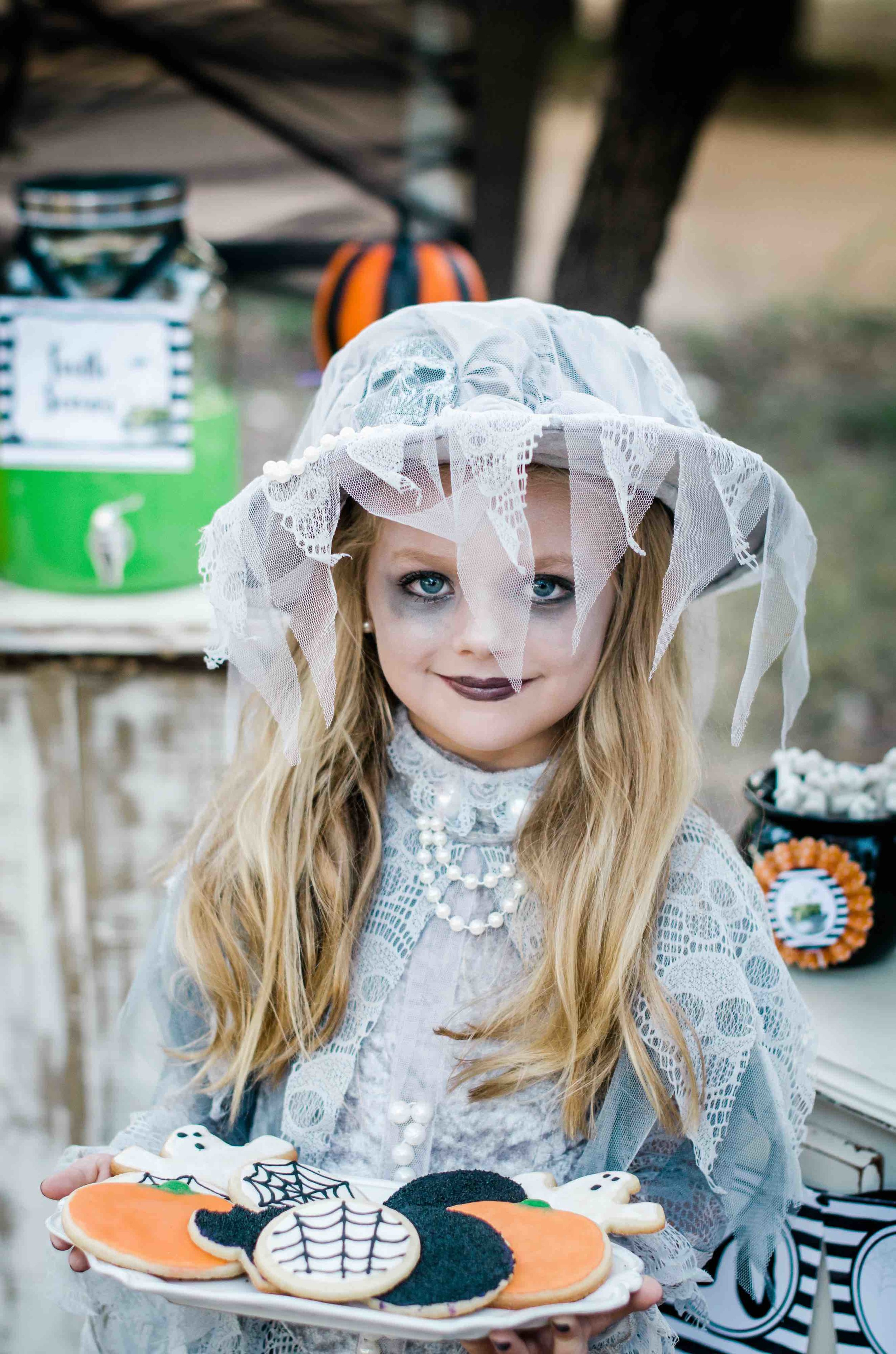 It's a Little Witches' Soiree Halloween Party with one amazing witch costume. This one features lace that has skulls all over it. Don't forget to add a little makeup to your girl to make her Halloween Witch costume comes to life. Click to see all the Halloween Party Ideas that you can re-create for your very own Halloween Kids Party. Styled by party stylist Mint Event Design. #halloween #partyideas #partyinspiration #halloweencostumes #halloweencookies #witchcostume #halloweendecorations