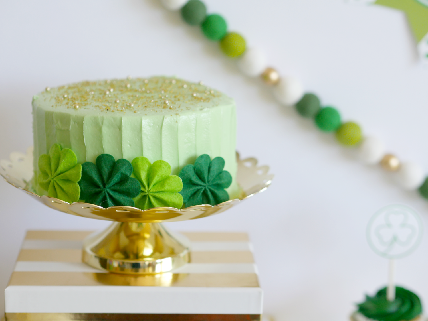 The prettiest mint green cake with gold sprinkles for Saint Patricks Day with pinwheel decorations. Party styling by Mint Event Design www.minteventdesign.com #partyideas #partydecorations #freeprintables #saintpatricksday #stpatricksday #shamrock #mintgreen #partycake