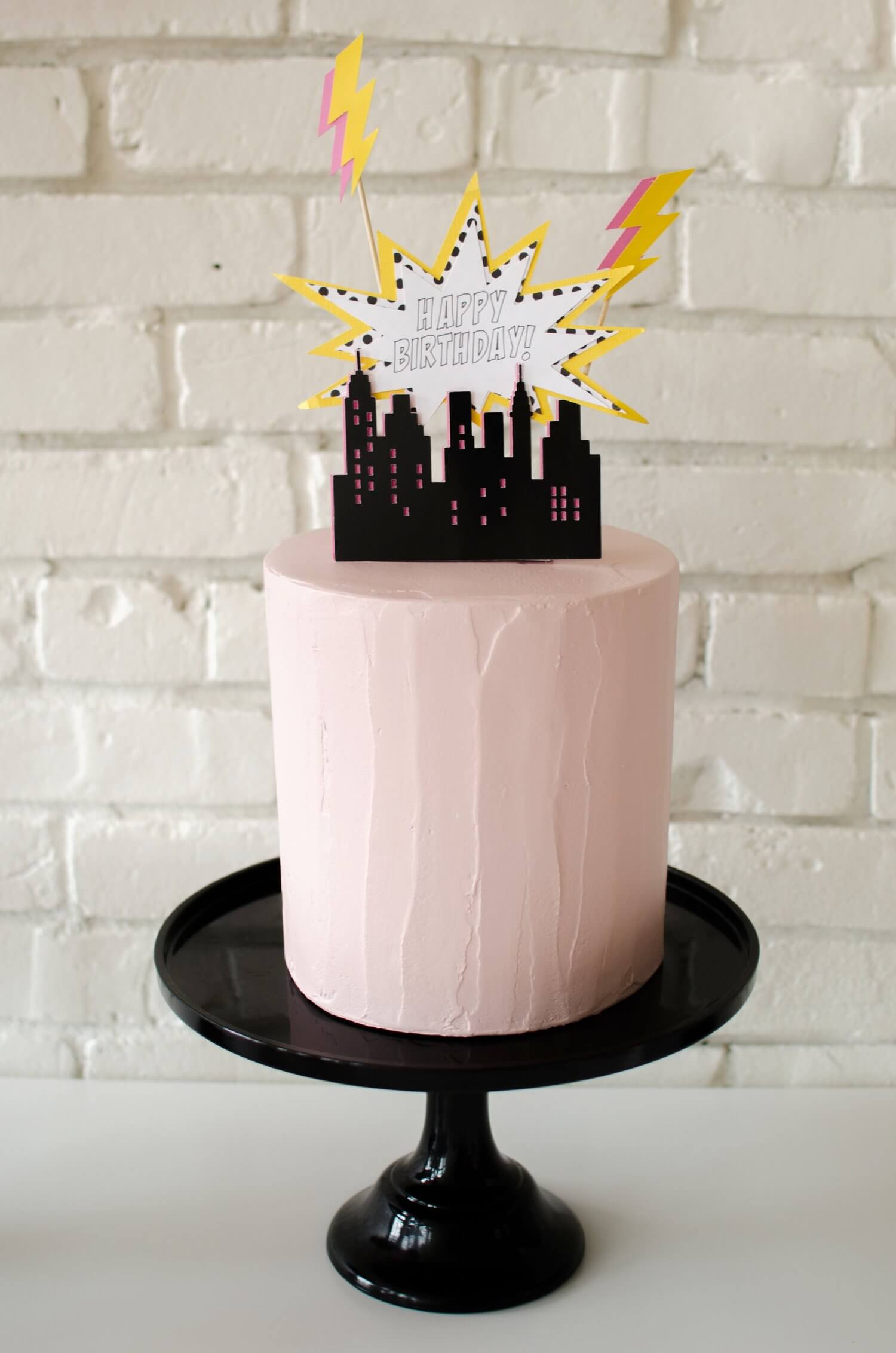 """Be sure to make your party cake make a statement - for this super hero birthday party, the cake was topped with a city skyline, lightening bolts and a burst shape that reads """"Happy Birthday"""" - see more kids party ideas on Mint Event Design www.minteventdesign.com #kidspartyideas #birthdaypartyideas #superheroparty #birthdayparty #partyideas #superhero #birthdaycake #birthdaycakeideas"""