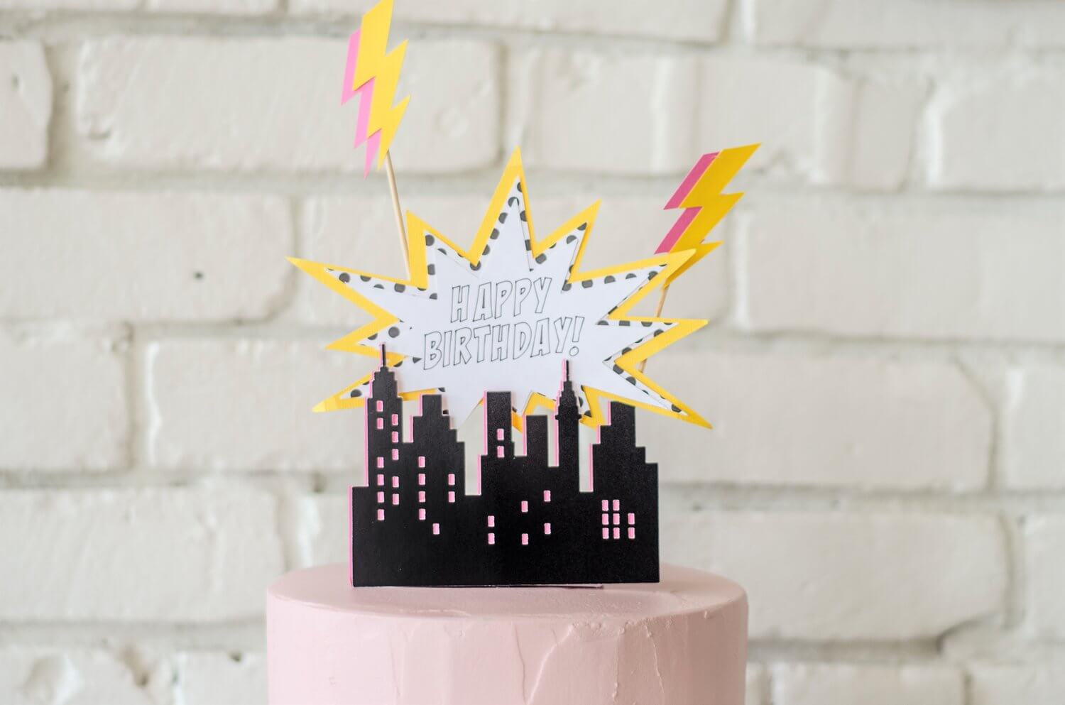 The best cake topper for a Super Hero Party - city skyline with lighting bolts and an eye-catching shape that reads Happy Birthday - see more kids party ideas on Mint Event Design www.minteventdesign.com