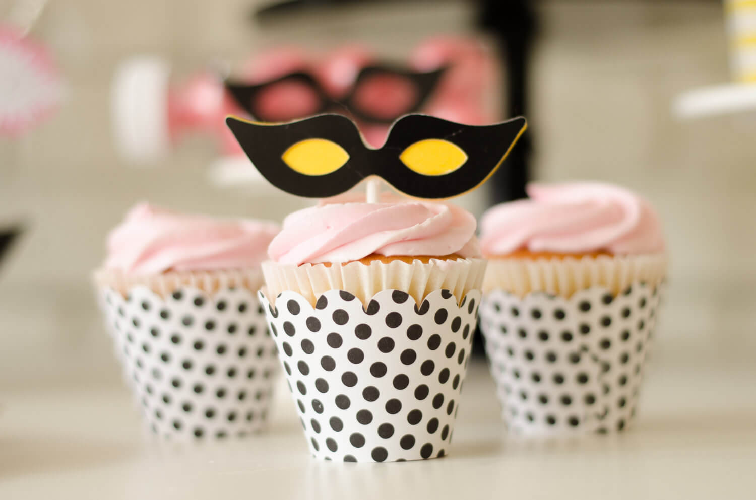 Polka dotted cupcake wrappers, pink frosting and a super hero mask topper are the perfect sweet for the girls at this super hero party - see more kids party ideas on Mint Event Design www.minteventdesign.com