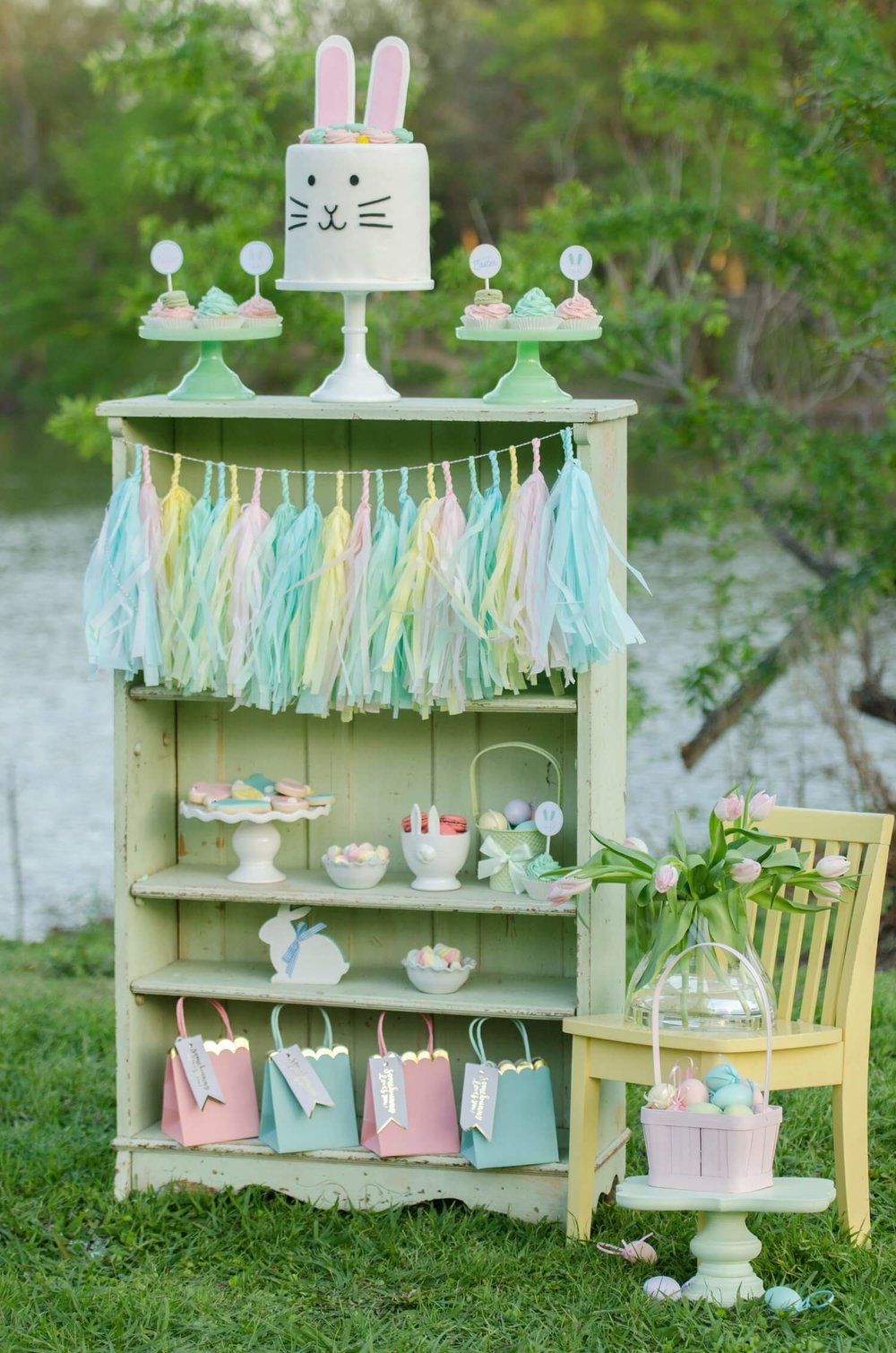 Be creative with your dessert table presentation. Here a mint colored shelf that matched the Easter party colors was used to display the party sweets, the cutest bunny cake and party favors. See more Easter Garden Party Ideas for Kids on Mint Event Design www.minteventdesign.com #easterparty #gardenparty #partysupplies #desserttable #eastertable