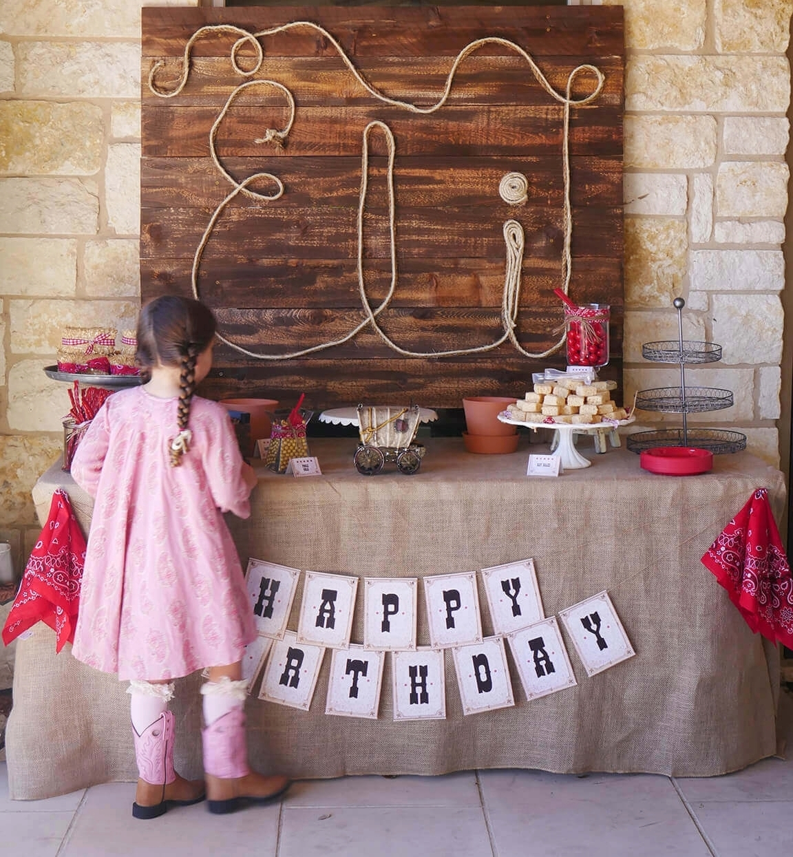 Personalized Rope Sign for a Wild West Birthday Party. Printable Happy Birthday banner hangs over the burlap table linen. Styled by Carolina from MINT Event Design / www.minteventdesign.com #wildwest #cowboy #birthdayparty #partyideas #desserttable #birthdaybanner