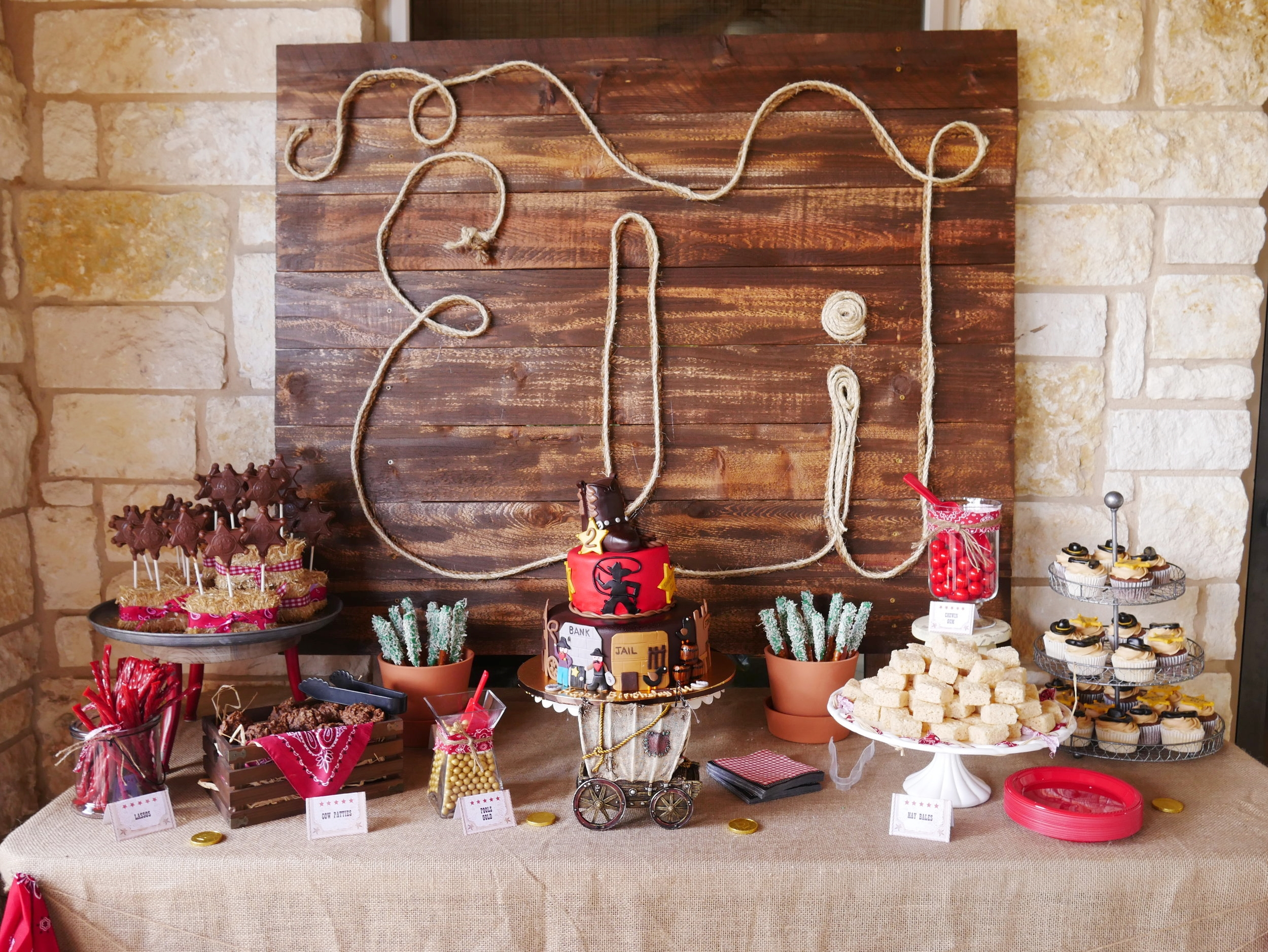 Wild West Birthday Party Dessert Table with a personalized rope sign backdrop / Styled by Carolina from MINT Event Design / www.minteventdesign.com #wildwest #cowboy #birthdayparty #partyideas #desserttable