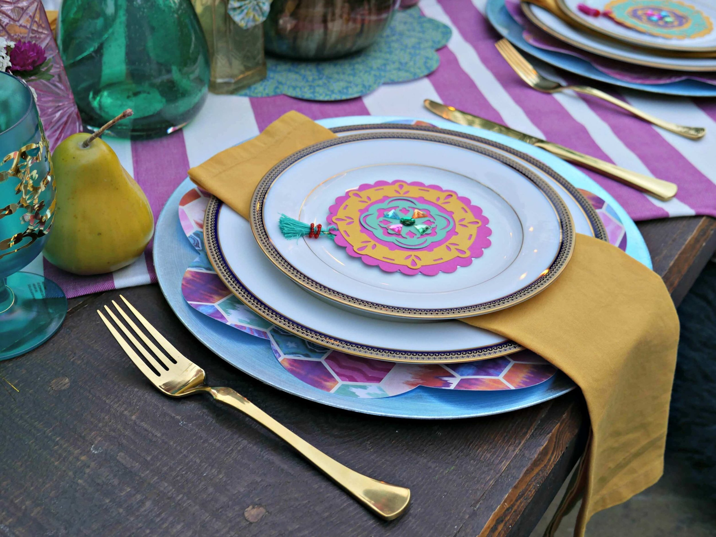 Gold utensils, colorful chargers, patterned paper and fancy plates set the tone at this boho chic engagement party. Styled by Mint Event Design www.minteventdesign.com #tablesetting #tablescapes #bohochic