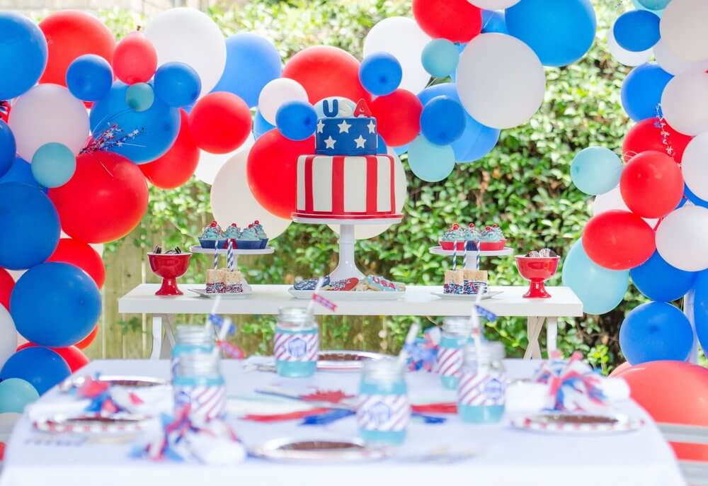 Patriotic 4th of July party inspiration including a USA cake centerepiece, balloon garland, and festive desserts.