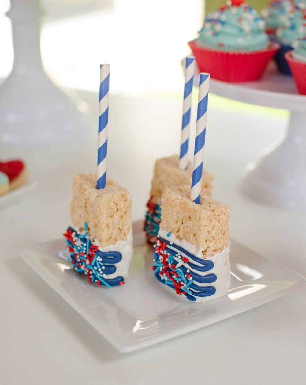 Rice Crispy type treats covered in icing and sprinkles, and skewered with a fun barbershop straw.
