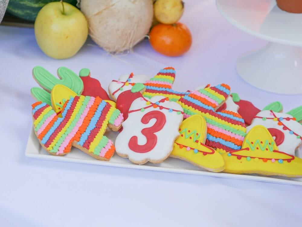 Pinata cookies, with sombreros, cactus, number 3, and chili peppers add to the fun Mexican fiesta Coco themed birthday party. Party Planning by Austin Texas party planner Mint Event Design www.minteventdesign.com #kidsbirthdayparty #fiestaparty #disneycoco #partyideas #girlbirthdayparty #cocobirthdayparty #sugarcookies