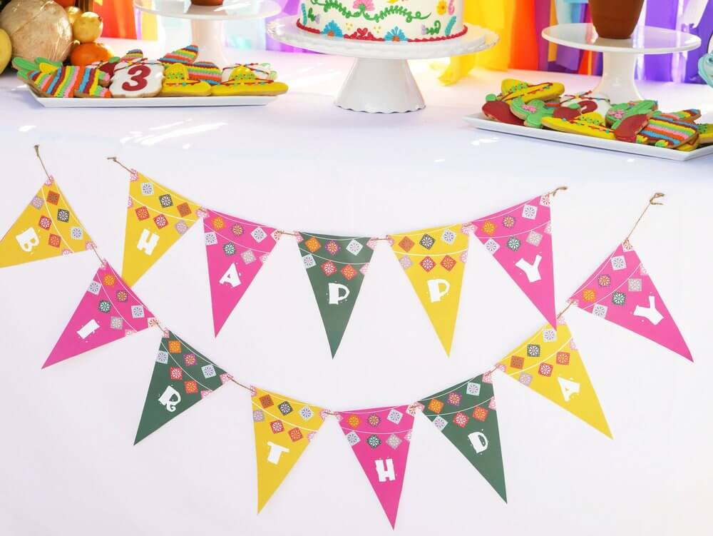 Create a 2-in-1 Party Banner. This Happy Birthday fiesta bunting banner was strung across the dessert table for the birthday girl and features a papel picado banner on the bunting. Party Planning by Austin Texas party planner Mint Event Design www.minteventdesign.com #kidsbirthdayparty #fiestaparty #disneycoco #partyideas #girlbirthdayparty #cocobirthdayparty #birthdaybanner #garland