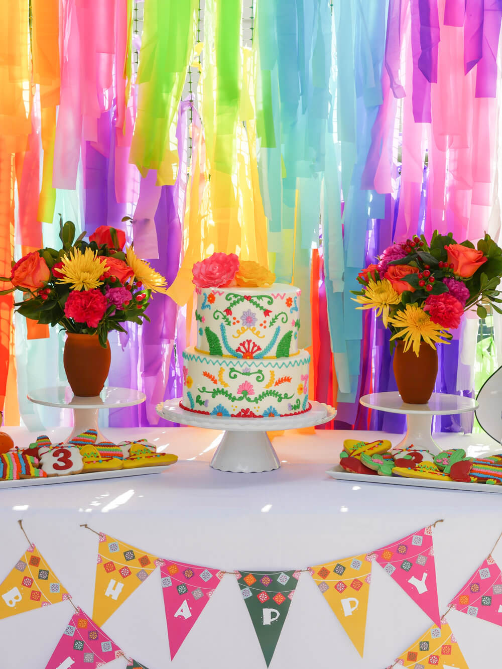 A Happy Birthday banner, Mexican fiesta cake, sombrero, cactus, pinata, and chili pepper cookies, along with fresh flowers and a fun streamer backdrop is the way to create the ultimate fiesta birthday party - inspired by the movie Coco. Party Styling by Austin Texas party planner Mint Event Design www.minteventdesign.com #kidsbirthdayparty #fiestaparty #disneycoco #partyideas #girlbirthdayparty #cocobirthdayparty