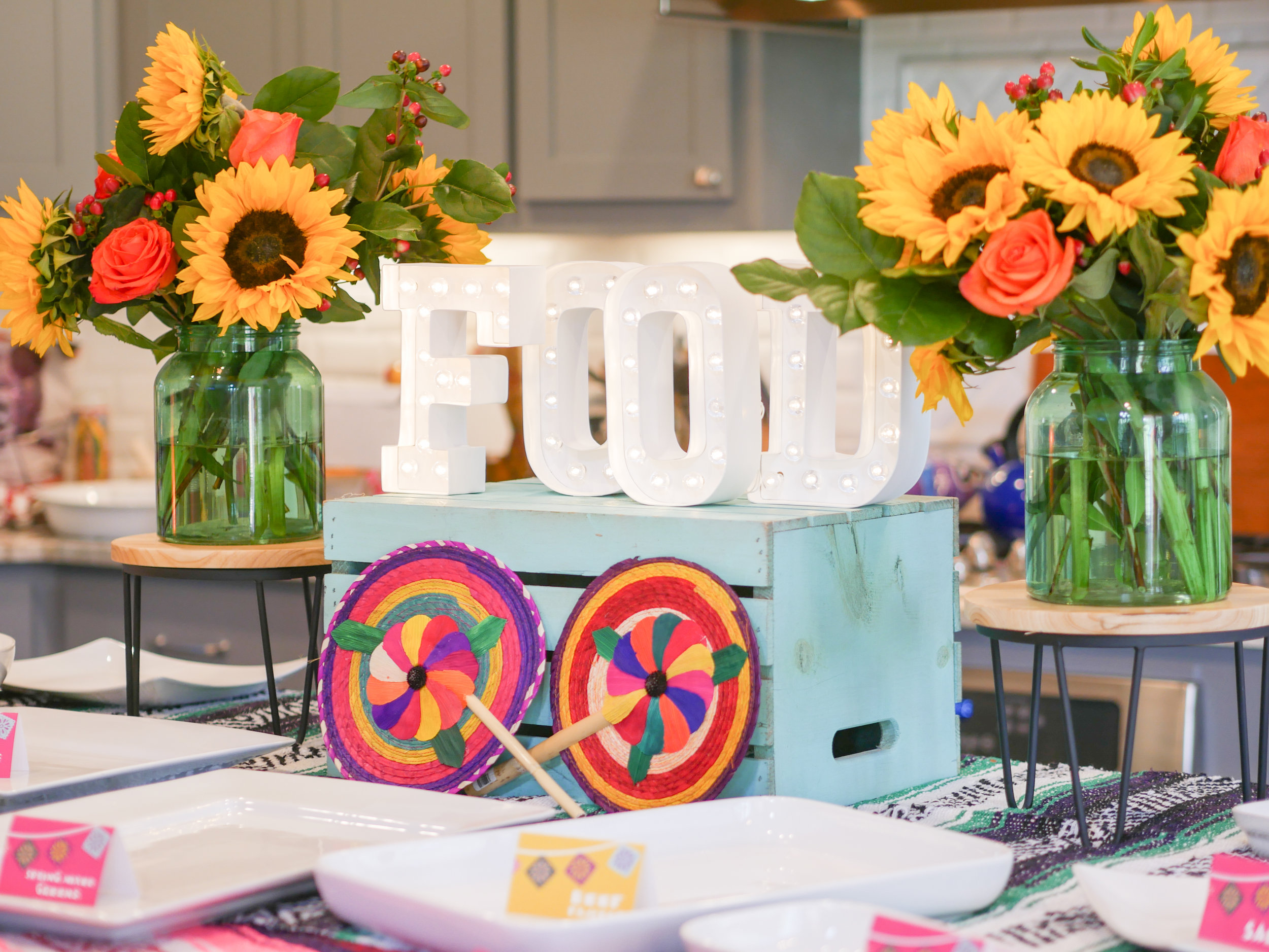 Create a fun and colorful food station for your fiesta party with colorful flowers and food labels. Styling by Austin Texas party planner Mint Event Design www.minteventdesign.com
