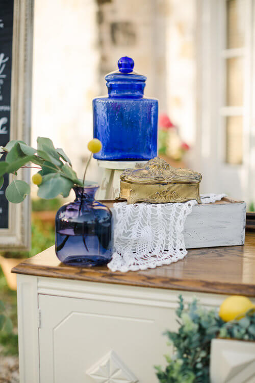 French country wedding inspiration, lace, vintage decor, blue glass. Vintage buffet furniture.